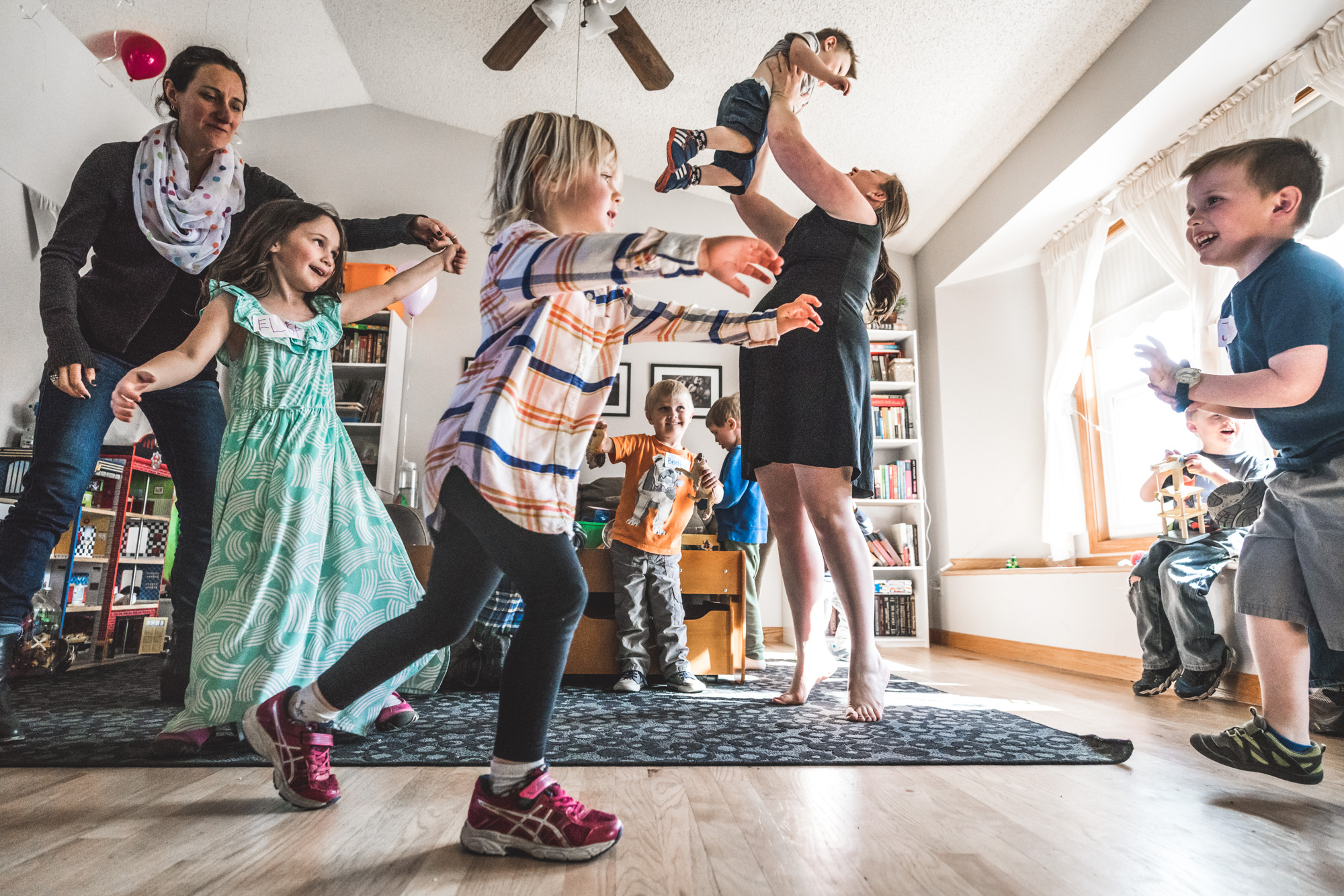 Color photo of both kids and adults dancing in a living room during a birthday party photography session in Aurora, Colorado