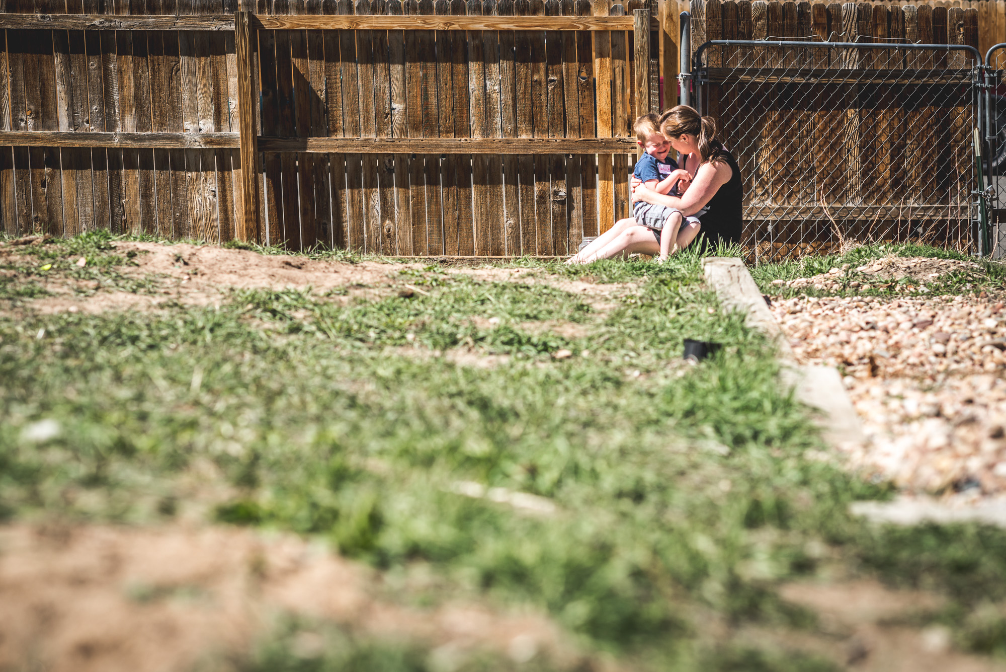 Color photo of a little boy sitting and crying on his mother's lap in their back yard as she comforts him
