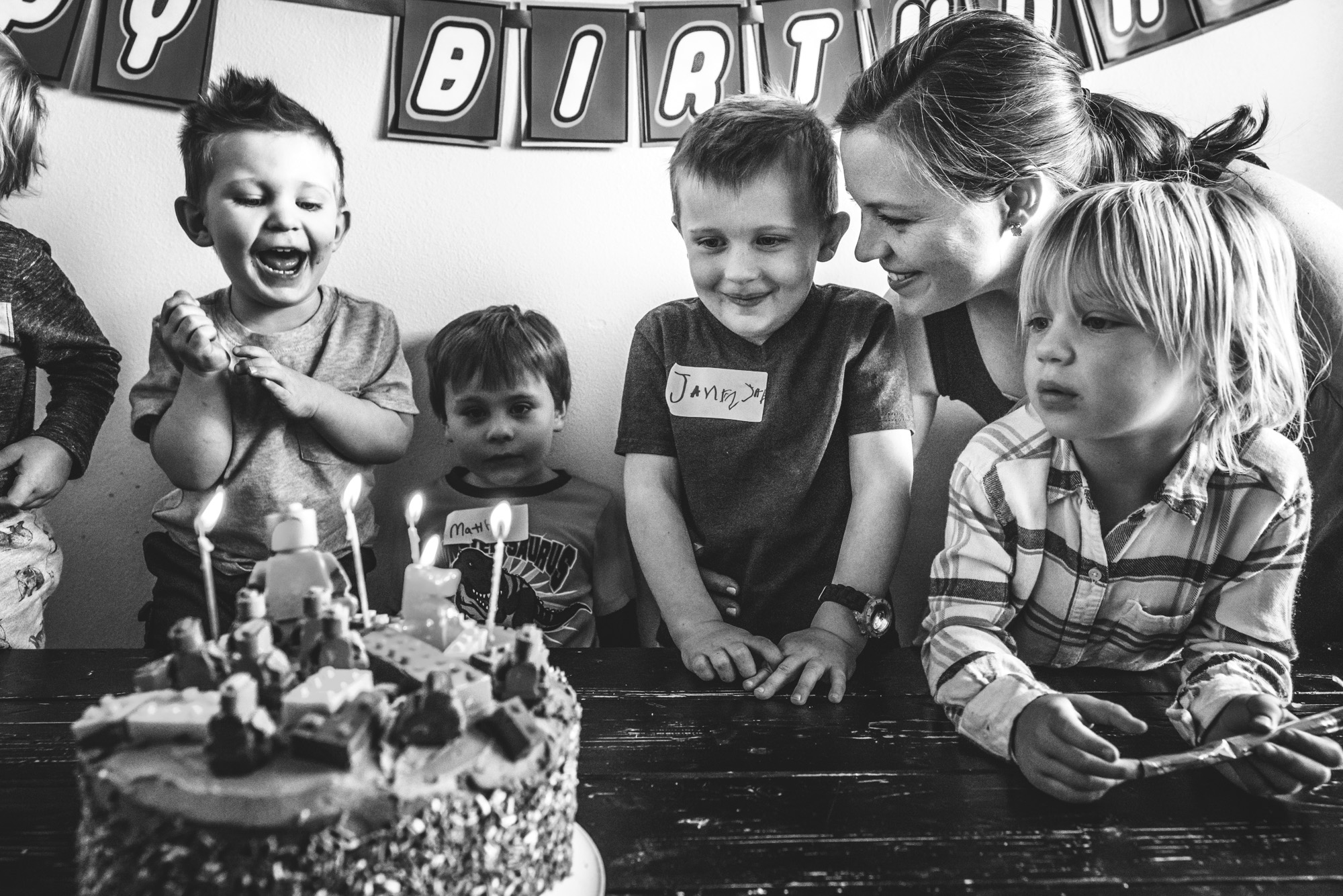 Black and white photo of a little boy at his birthday party, getting ready to blow out his candles as his friends gather round him and his mother smiles on