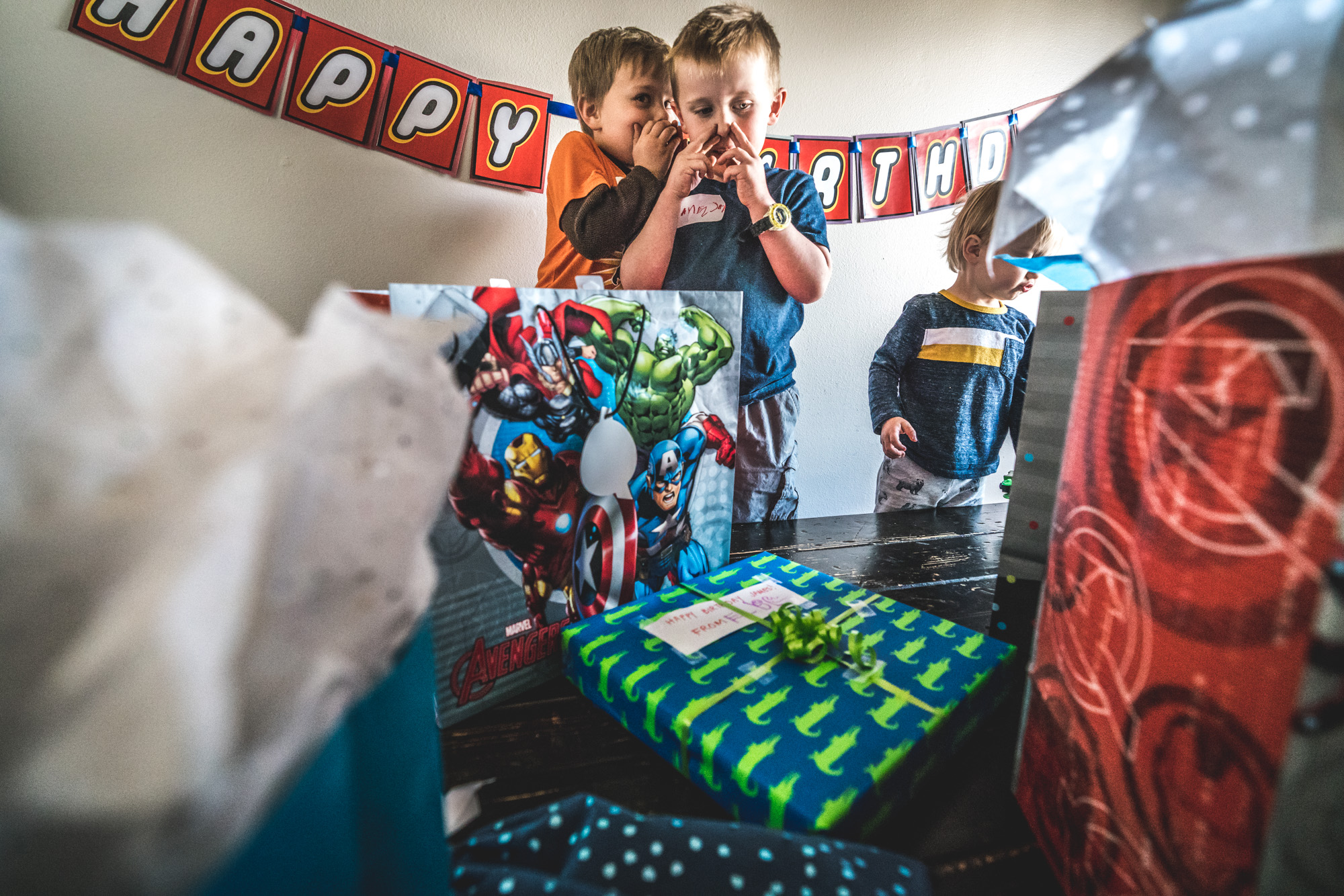 Photo of two little boys surrounded by colorful birthday presents as one little boy whispers to the other