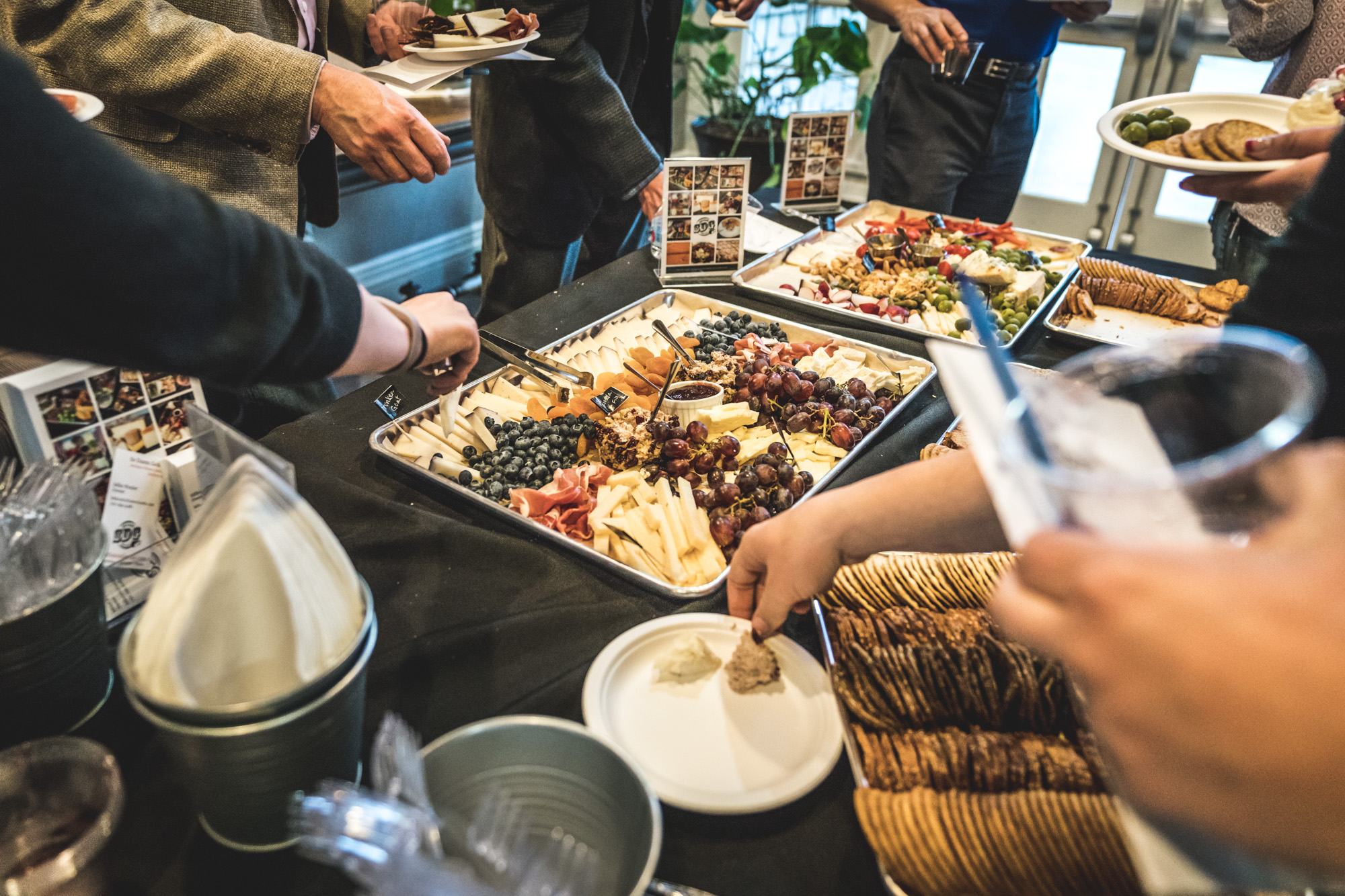 Color photo of beautiful meet and cheese trays on a table as people reach in to grab food. Taken during the Autism Society of Colorado's Wine Competition event in Denver, Colorado