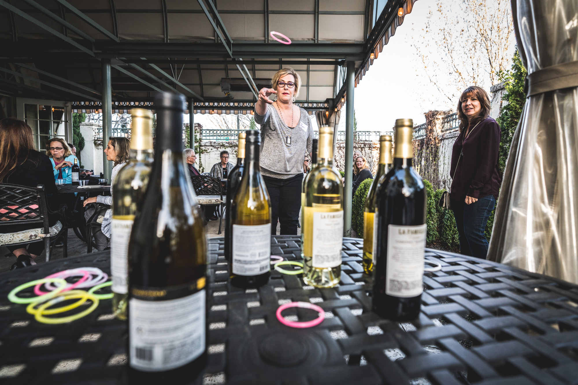 Color photo of a woman tossing rings at bottles of wines on a table during an Autism Society of Colorado Wine Competition fundraiser in Denver.