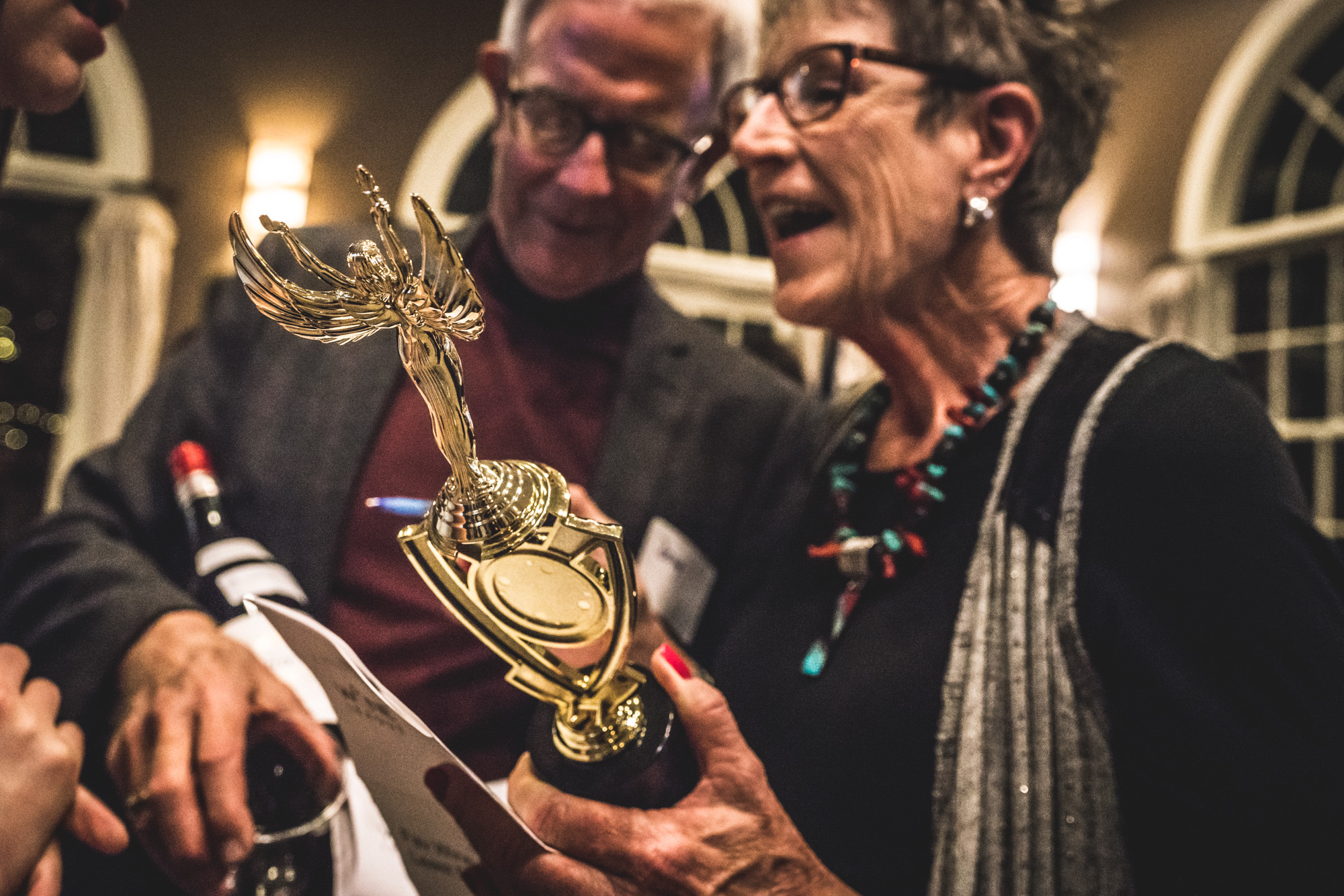 Color photo of a woman and man holding the trophy they won at a competitive wine drinking competition in Denver, CO.