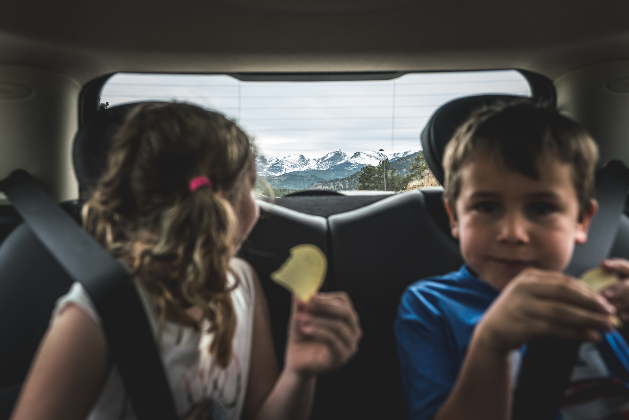 Color photo of two young children in the back seat of the car as the young girl looks behind her to look at the snow covered Rocky Mountains behind them. Taken during their documentary family photography photo session in Estes Park, Colorado