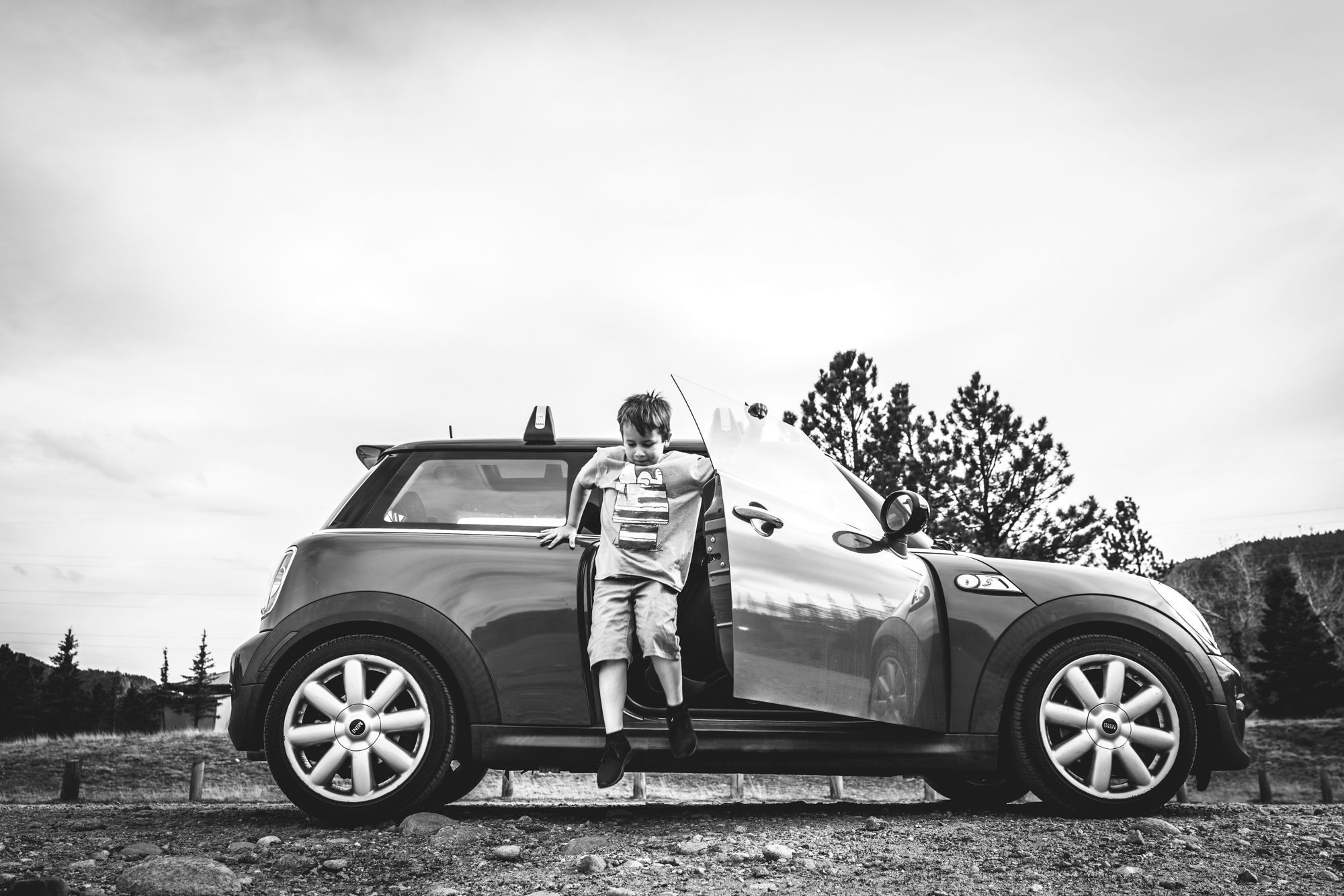 Black and white photo of a boy mid-air as he jumps out of a mini cooper. Taken during his mini adventure photo session in Estes Park, Colorado.