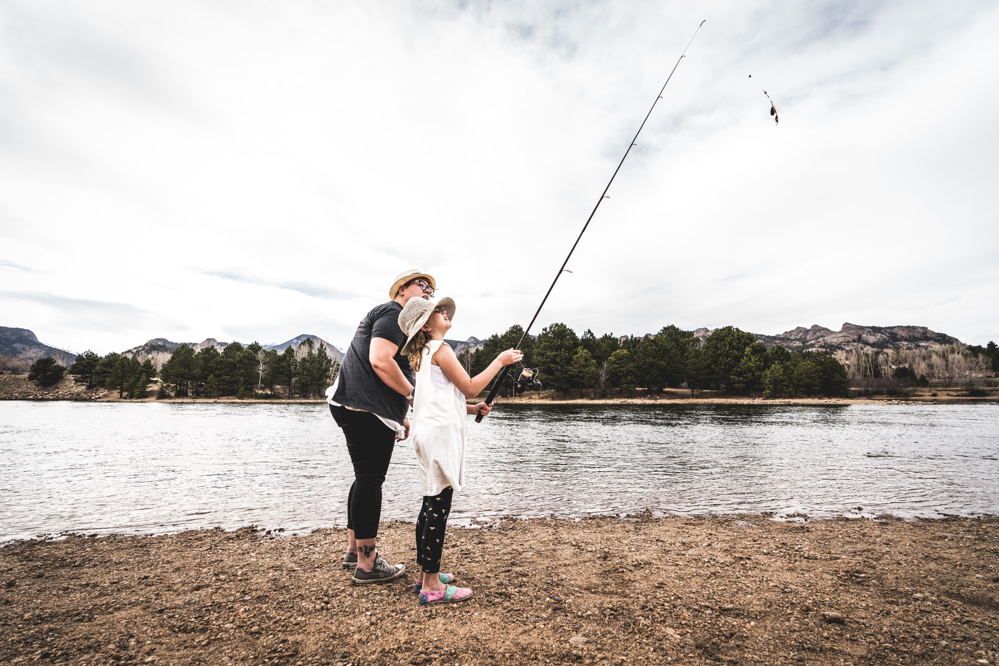 Color photo of a mother and daughter looking up to the top of the fishing pole held by the young girl. Taken in front of a lake in Estes Park, Colorado.