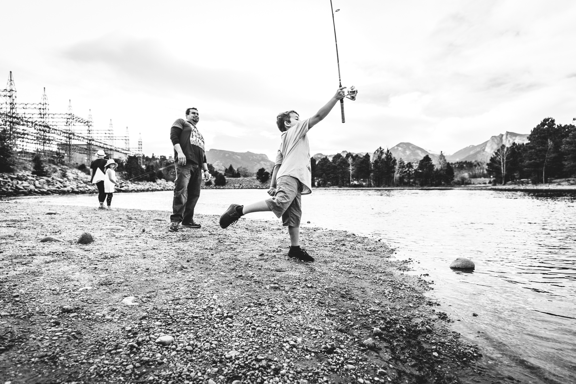 Black and white photo of a little boy at a lake attempting to cast a fishing rod, one leg thrown up behind him from the effort of it, as his father, who is standing next to him, leans back to avoid getting hit. Taken at a lake in Estes park, Colorado.
