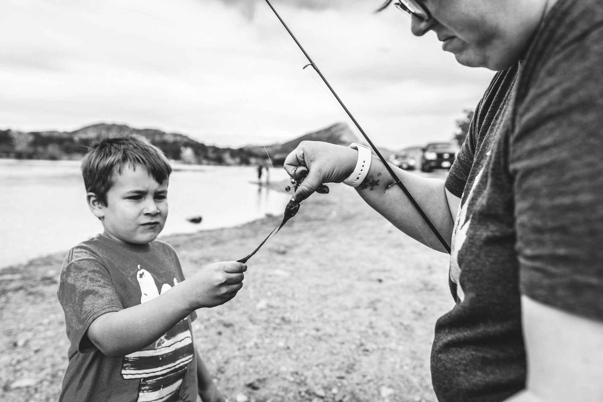 Black and white photo of a mother holding onto a fishing rod covered in algae as her young son attempts to pull the algae off. Taken by a lake in Estes Park, CO.