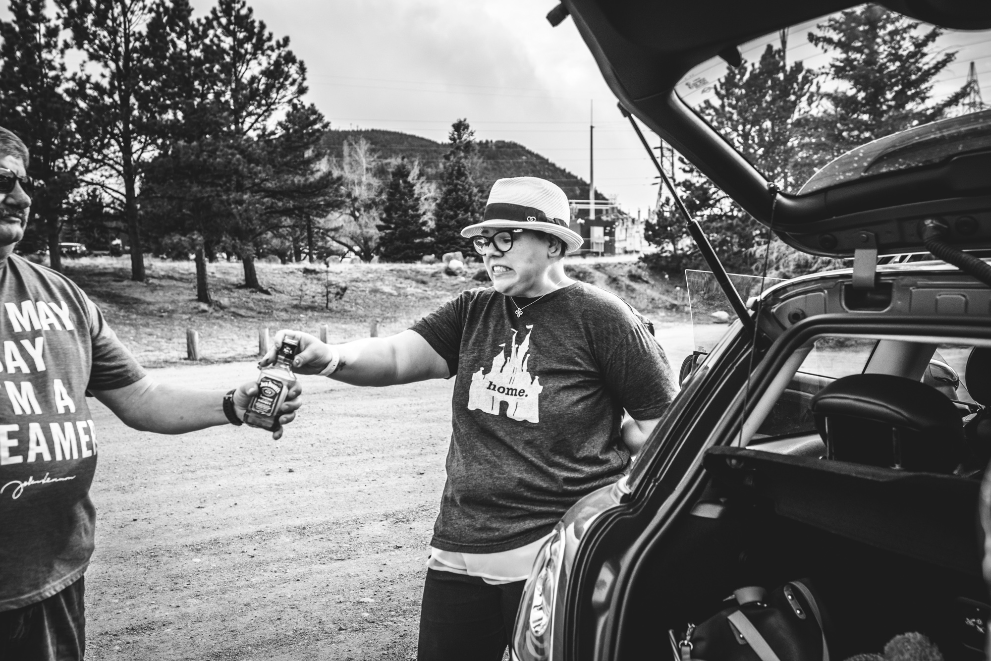 Black and white photo of a woman and a father standing by her car. The woman hands a bottle of Jack Daniels to her father and makes a funny face after having taken a drink of it. Taken by a lake in Estes Park, Colorado.