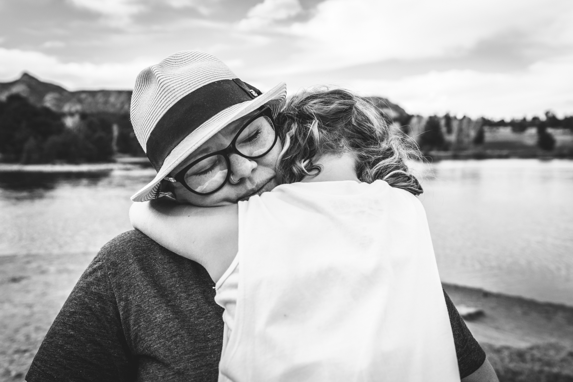 Photo of a woman holding her daughter tight as she closes her eyes. Taken in front of a lake in Estes Park, CO.
