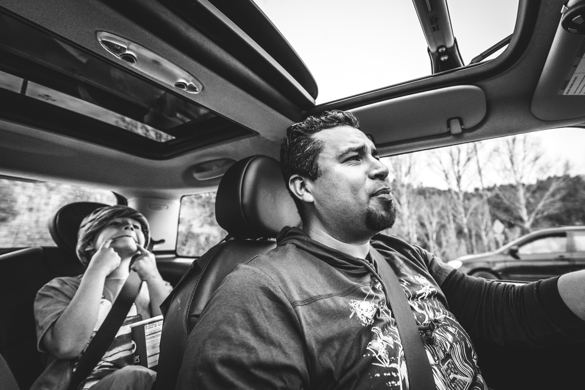 Black and white photo of a father driving a car as his son makes a funny face at him from the back seat.