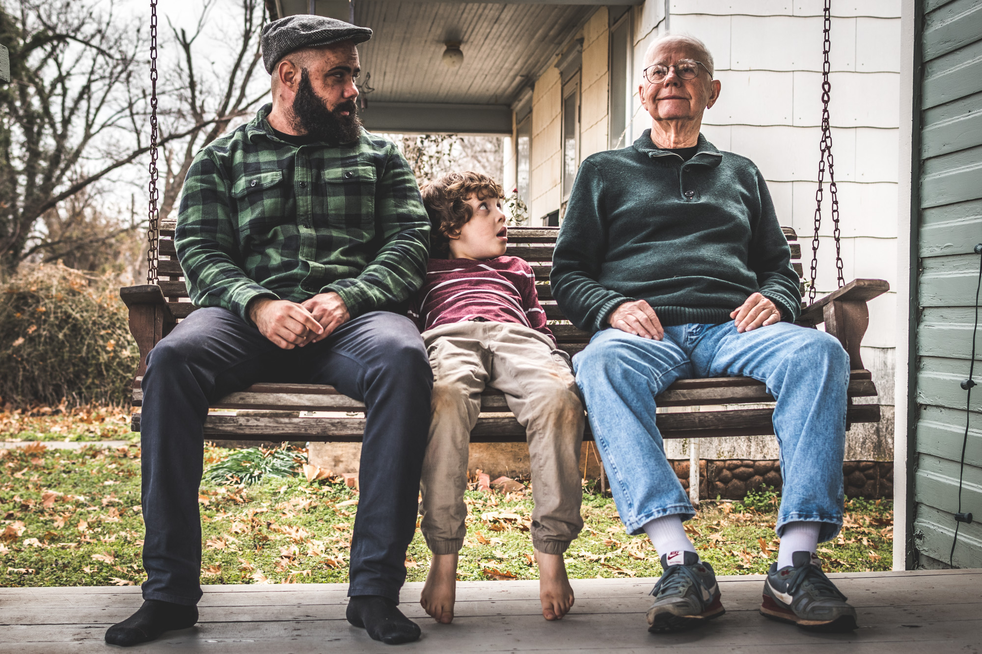 Color photo of three generations of men sitting on a front porch swing, the youngest boy of 7 years in the middle, covered in dirt, a middle aged man to his left wearing plaid and a hat, and the grandfather/great-grandfather to the right, wearing warm, comfortable clothes and staring off into the distance