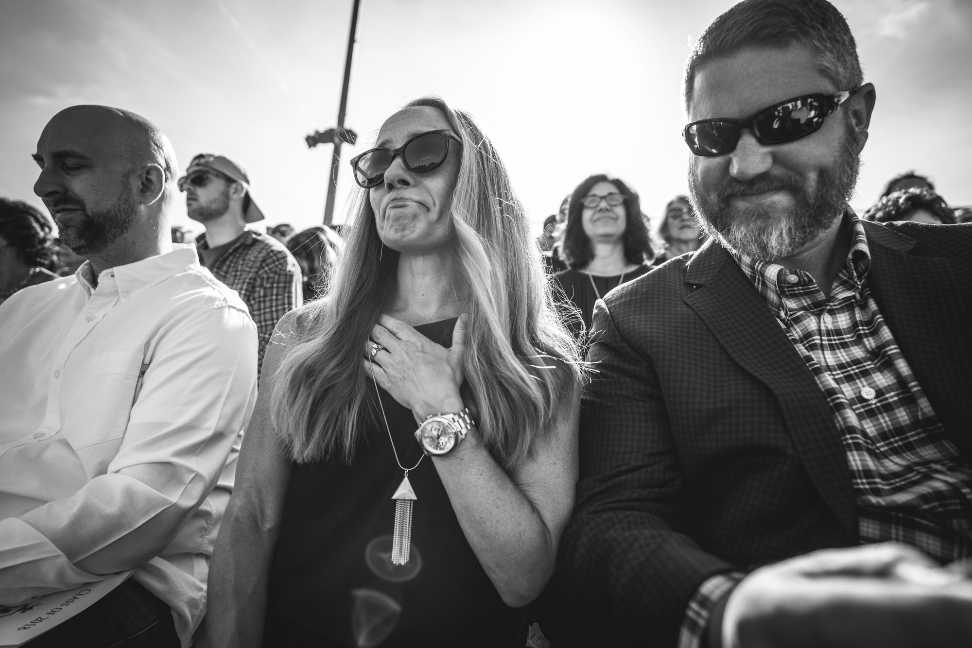 Black and white photo of a woman sitting in the bleachers at her son's graduation ceremony with her hand to her chest, crying tears of joy.