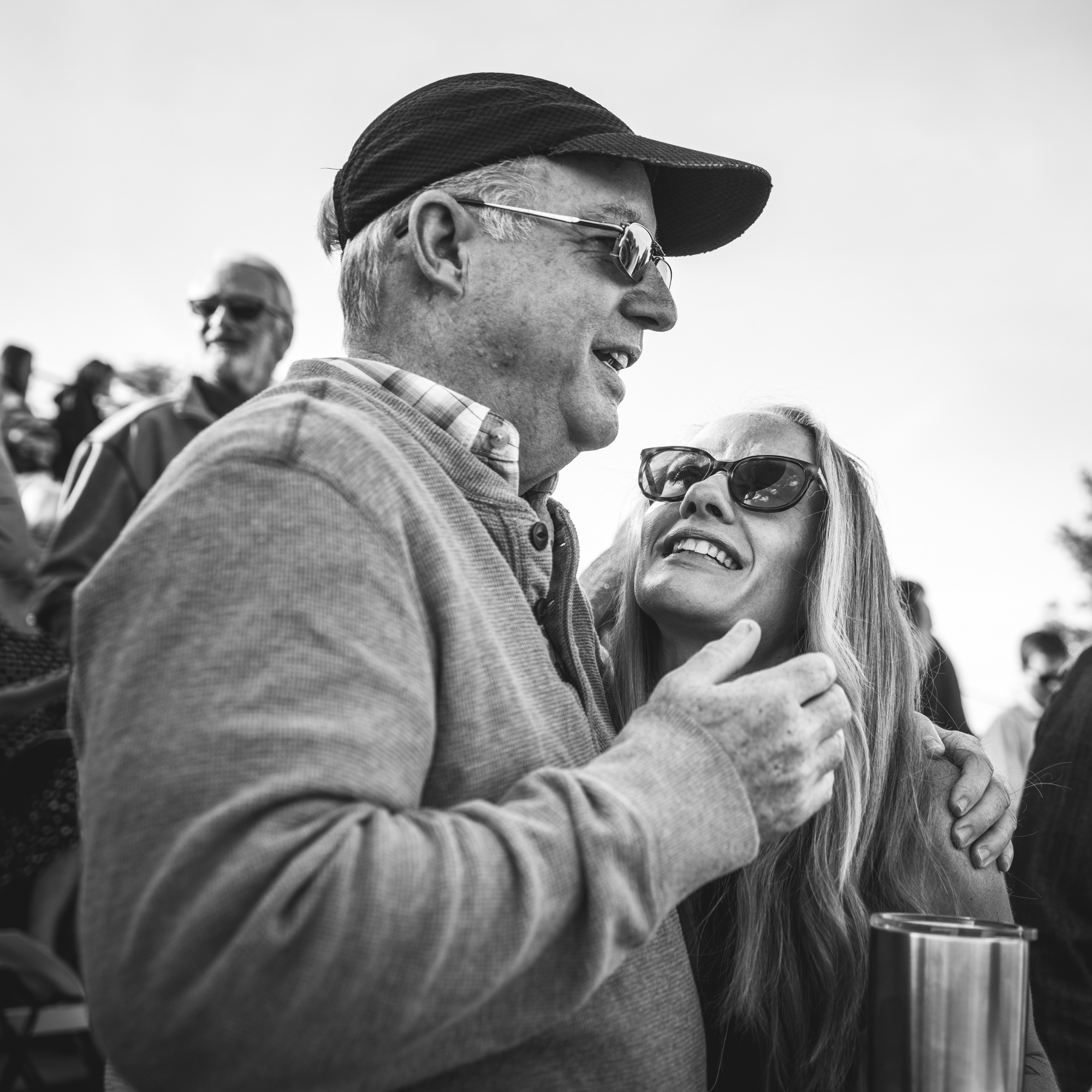 Black and white photo of a woman looking up at her dad and smiling, Denver, Colorado