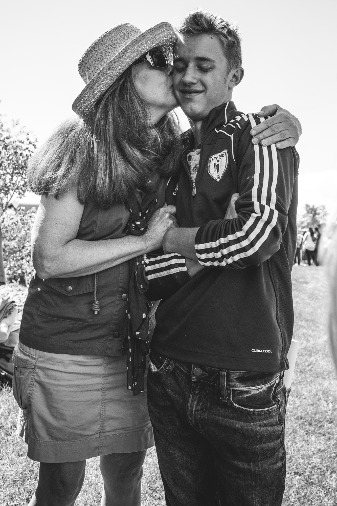 Black and white photo of a grandmother kissing her teenage grandson on the cheek. Denver, CO