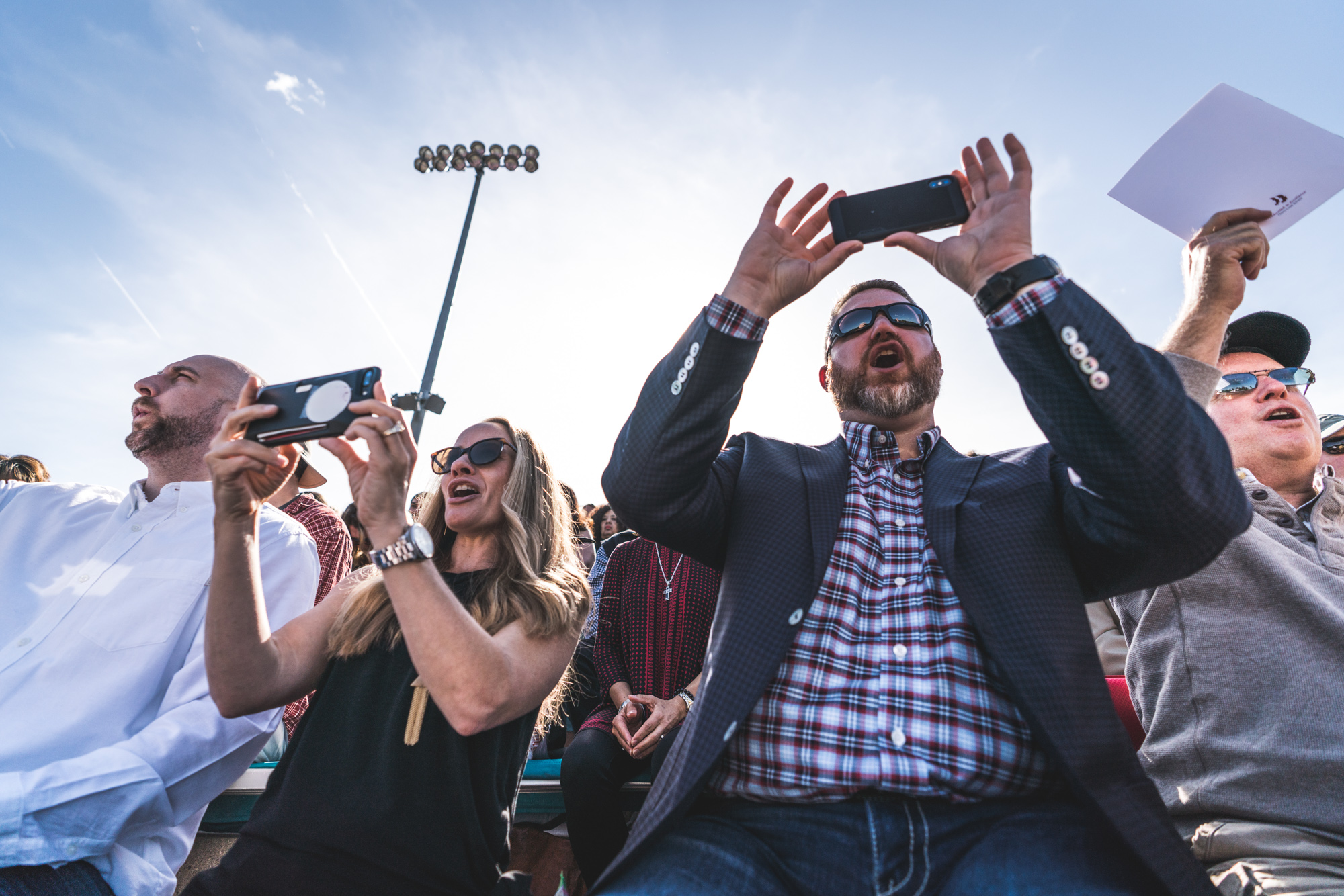 Color photo of a family sitting in bleachers, screaming for their son as he walks across the graduation stage. Taken at Cherry Creek High School in Denver, Colorado.