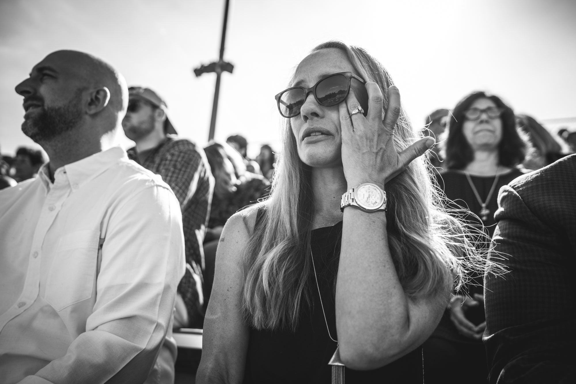 Black and white photo of a woman wiping tears from her eyes as she sits in the bleachers at her son's high school graduation ceremony.