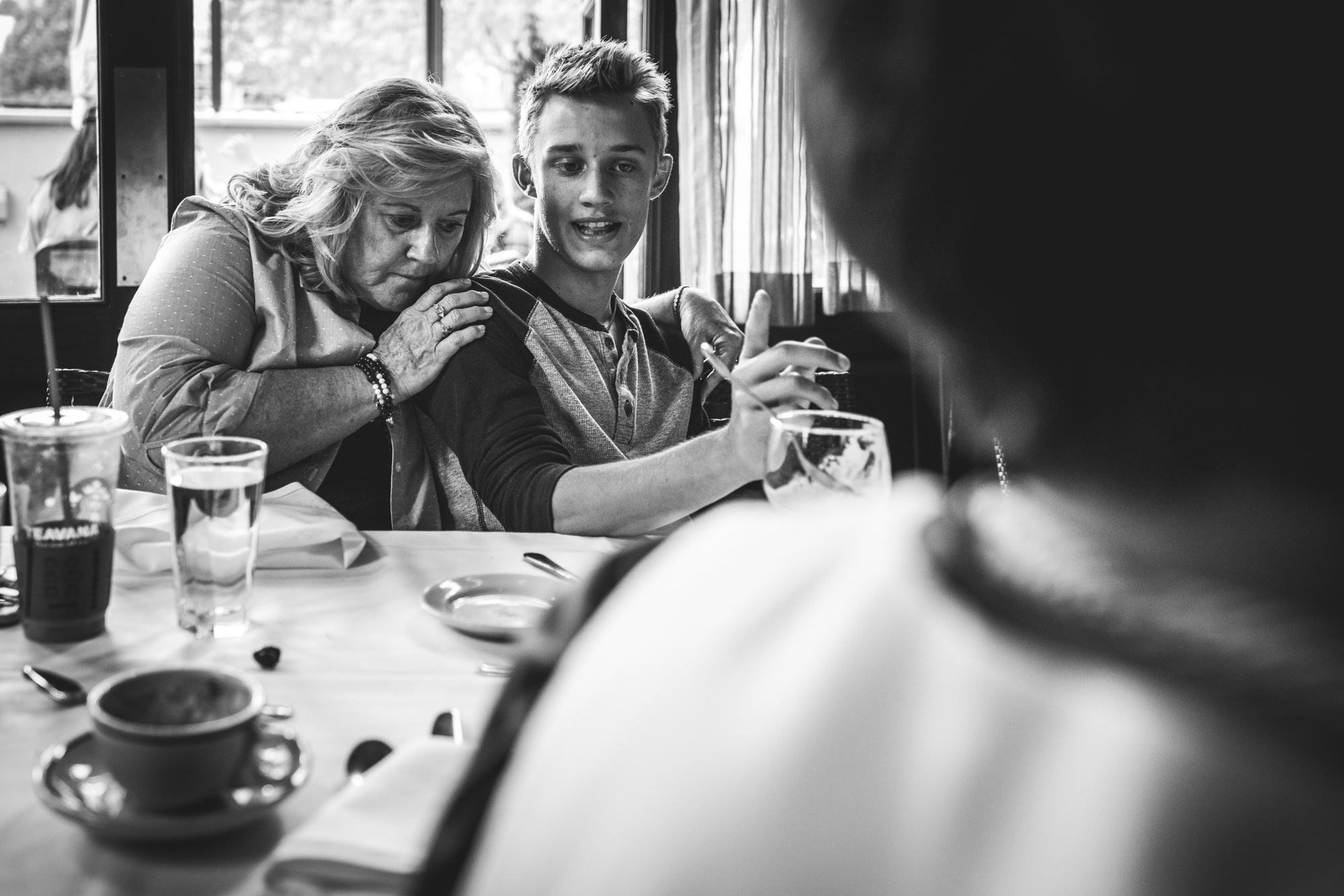Black and white photo of a grandmother and grandson at a restaurant. The teenage grandson talks while his grandmother leans on and hugs him. Taken during a documentary event photography session in Denver, Colorado.
