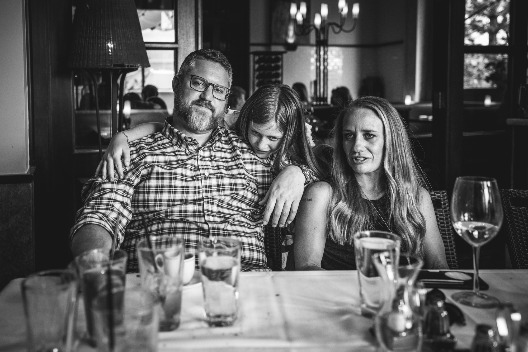 Black and white photo of a mother and father sitting at a table at a restaurant while their teenage daughter hugs her dad from behind. Taken in Denver, Colorado.