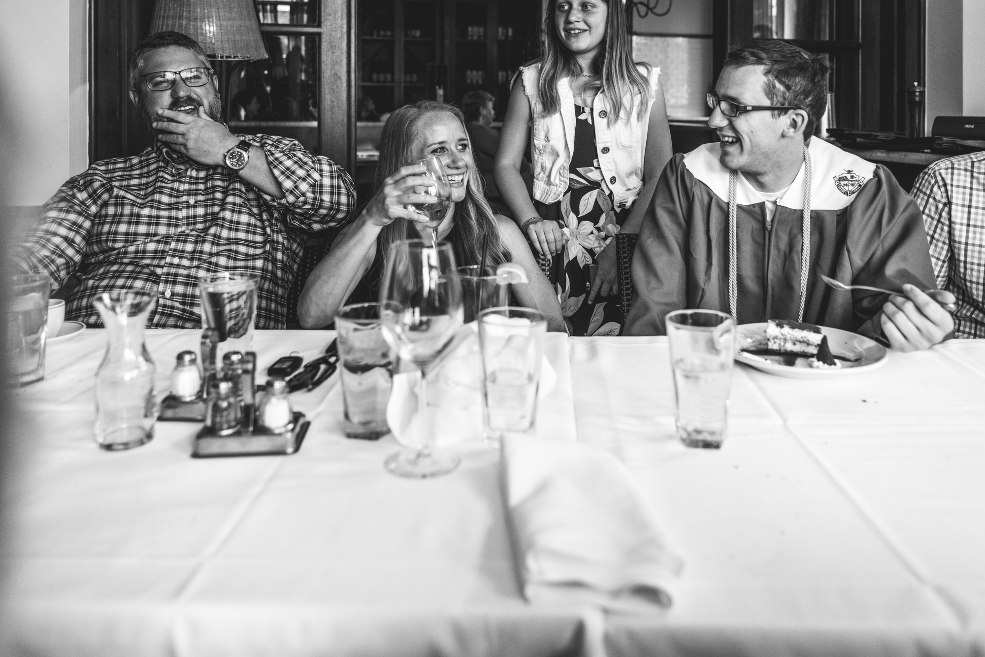 Black and white photo of a family at a restaurant together, the mother looking over and smiling at her teenage son, who has just graduation high school and is wearing his cap and gown.