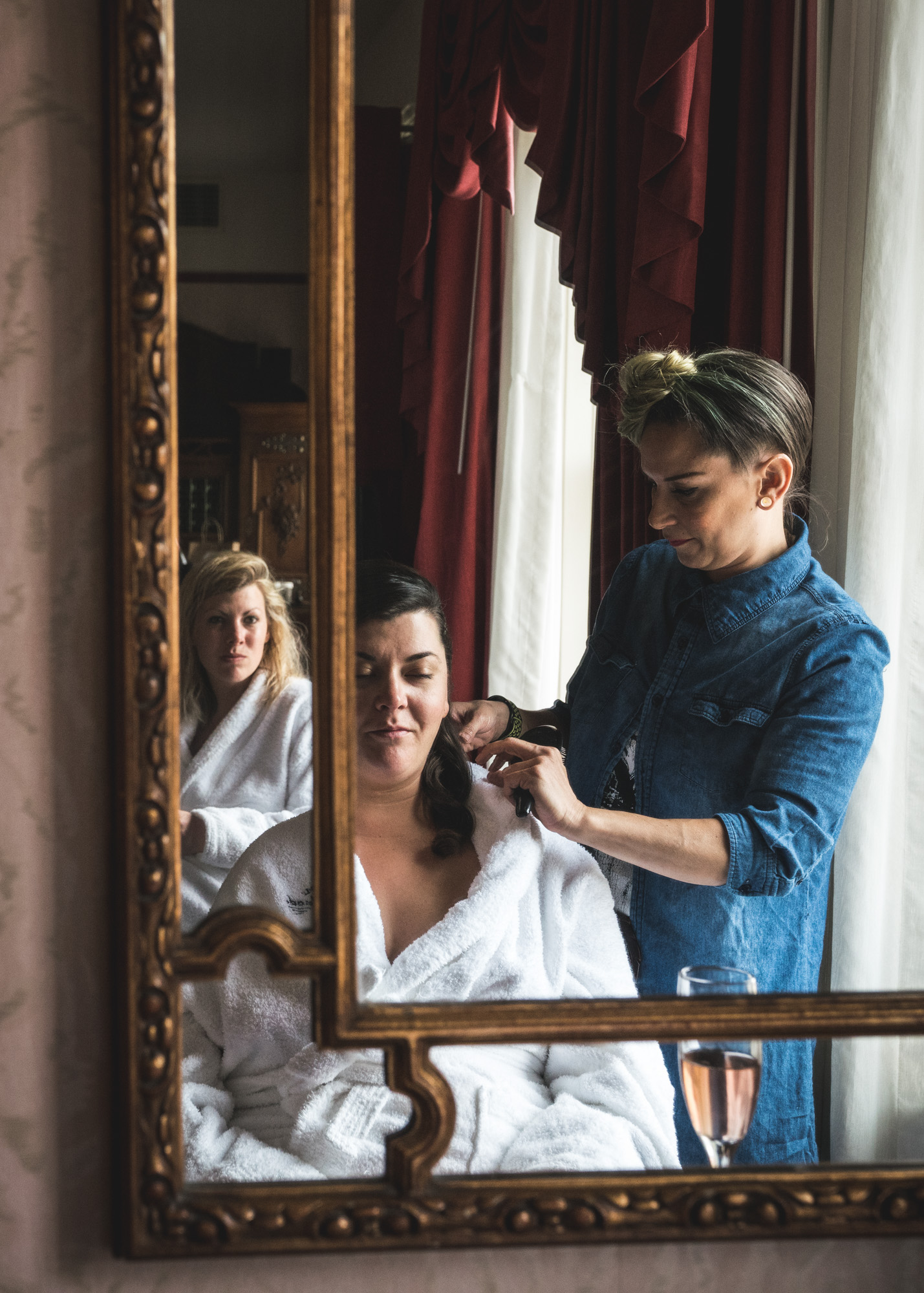 Color photo of woman wearing a white robe having her hair fixed by a woman in a blue shirt and blue streak in her hair with her blond friend in the background, also wearing a white robe, all of this reflected in a gilded mirror. Taken during the bride's wedding preparation photography session in their hotel suite in the Hotel Boulderado in Boulder, Colorado