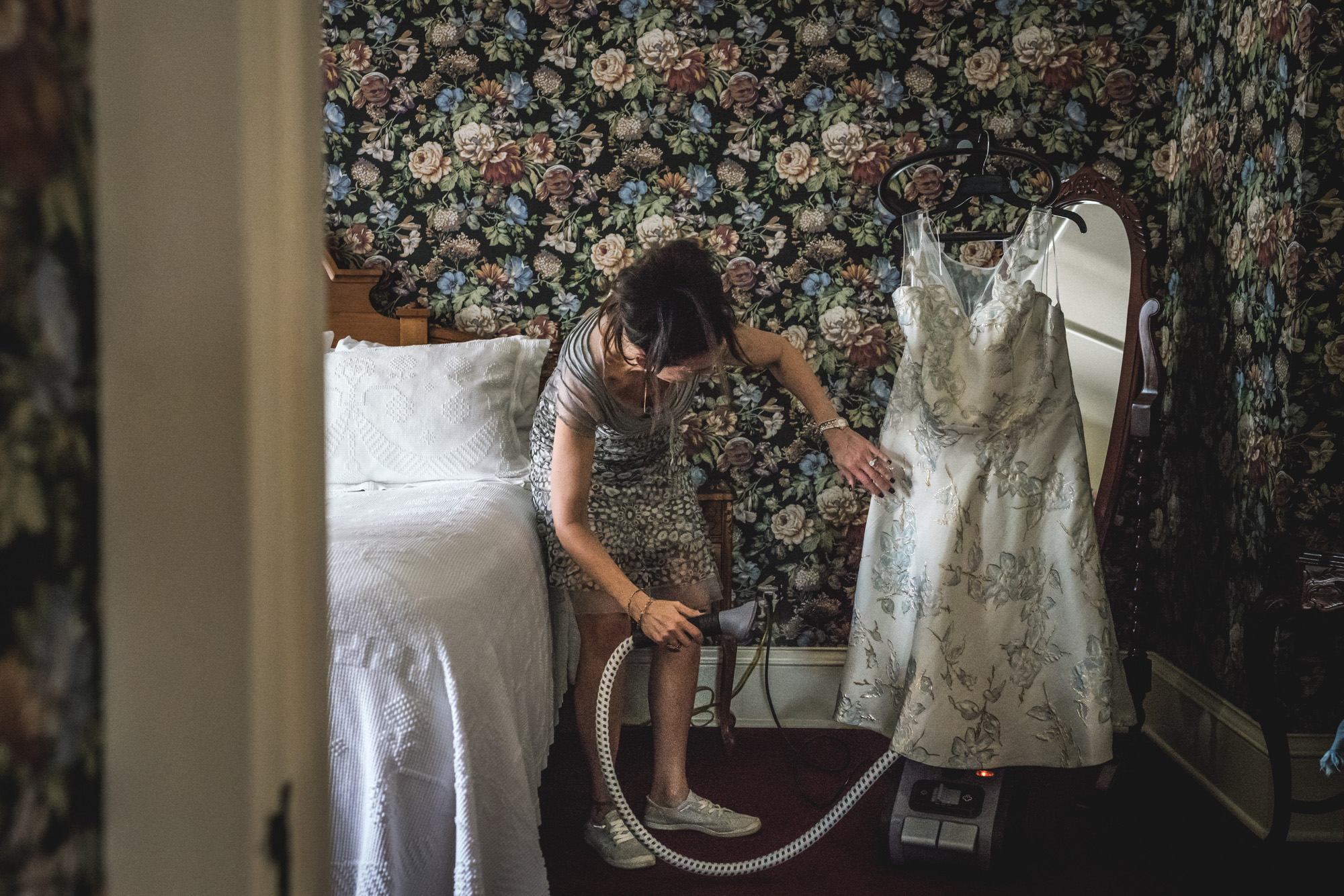 Color image of a woman in a dress and sneakers steaming a flowery dress in a flowery, ornate hotel room.
