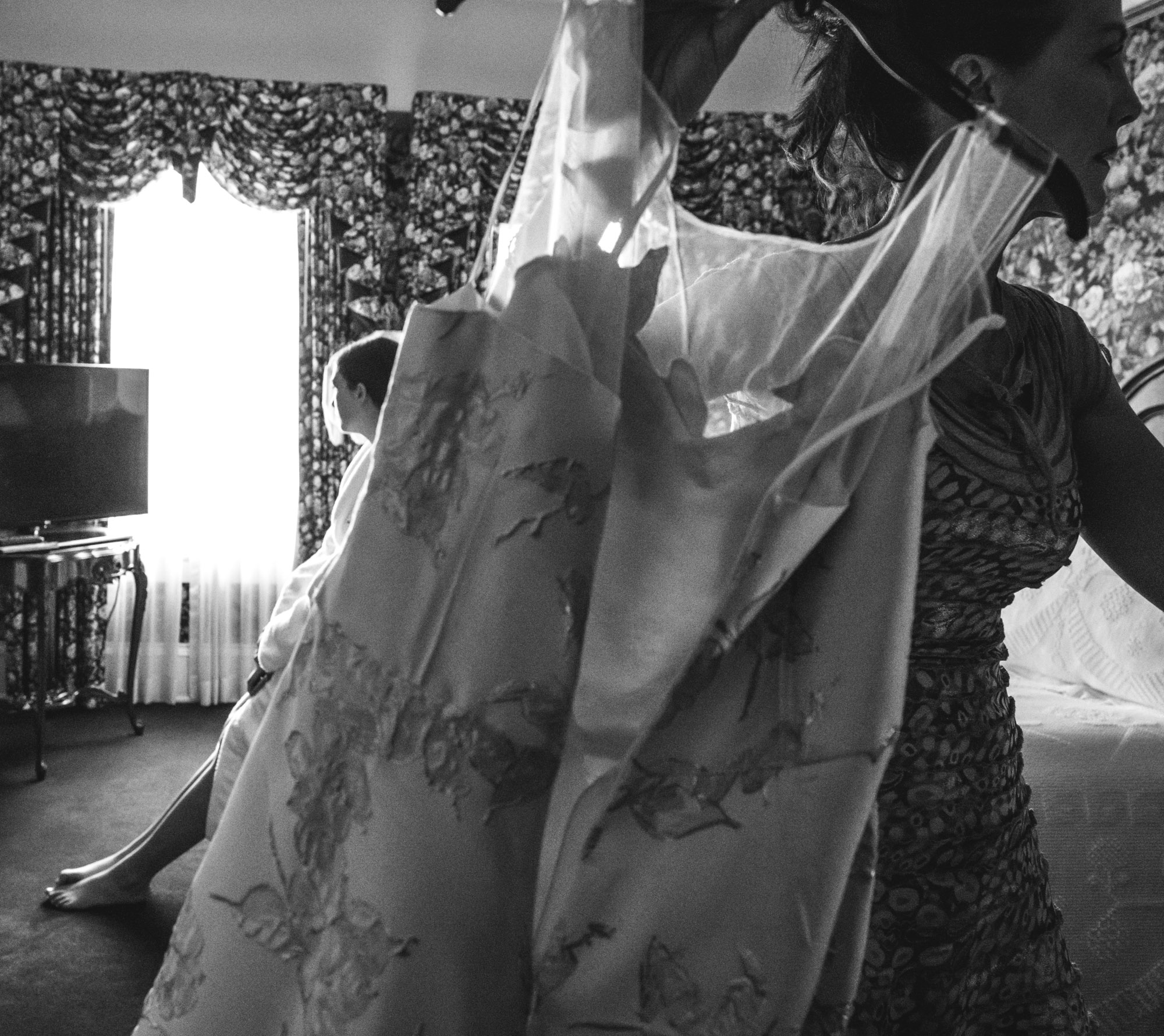 Black and white photograph of a woman holding up a dress in the foreground as a young girl reclines on the bed behind her in an opulent hotel suite in the Hotel Boulderado in Boulder, CO. Taken during wedding preparations.