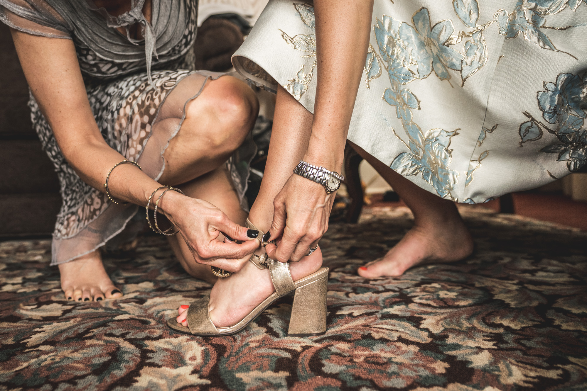 Color photo of a woman in a beautiful blue dress getting help from another woman in a dress getting her shoes on. Taken during her wedding day preparations in the Hotel Boulderado in Boulder, CO.