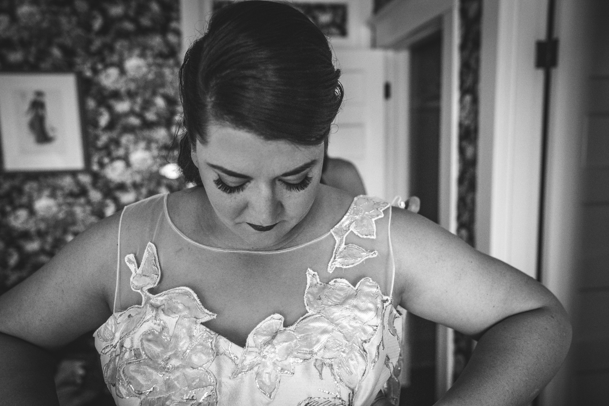Black and white photo of a bride putting on her gown in her hotel room in Boulder, Colorado.