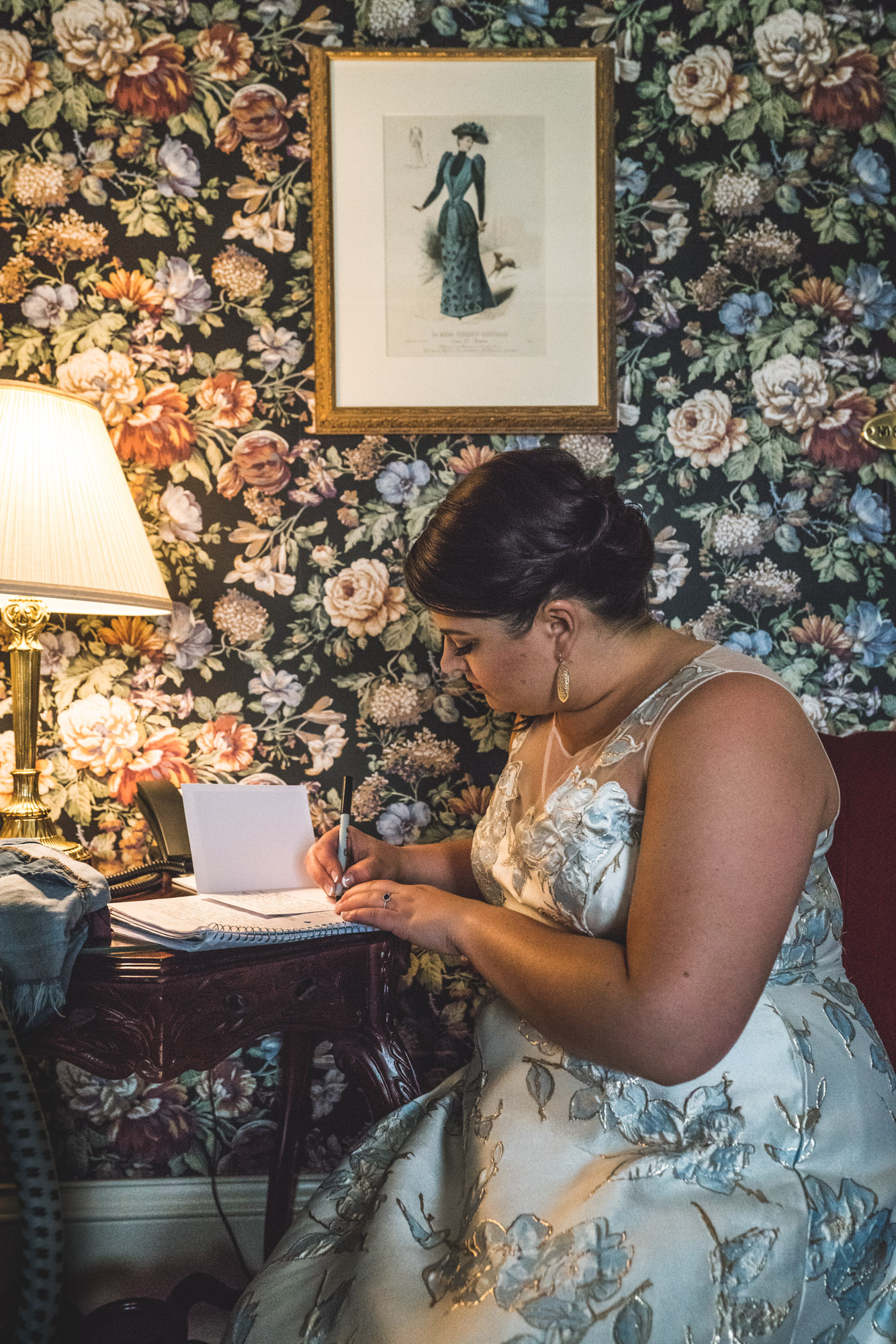 Color photo of a bride in a blue floral dress writing her vows in her bridal suite covered in floral wallpaper. Taken in Boulder, Colorado.