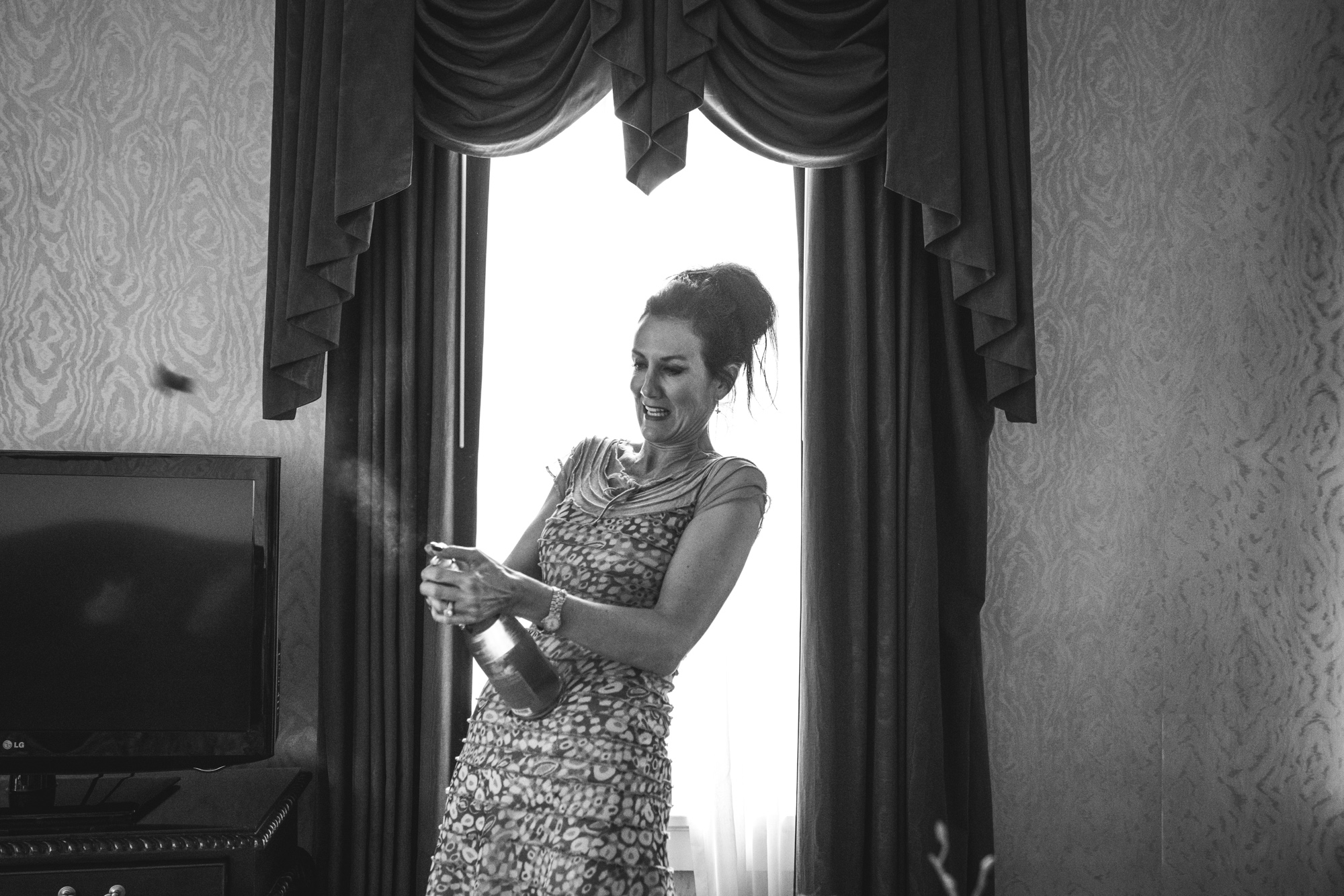 Black and white photo of a woman in a formal dress, popping off the cork of a champagne bottle in a beautiful hotel suite at the Hotel Boulderado in Boulder, CO
