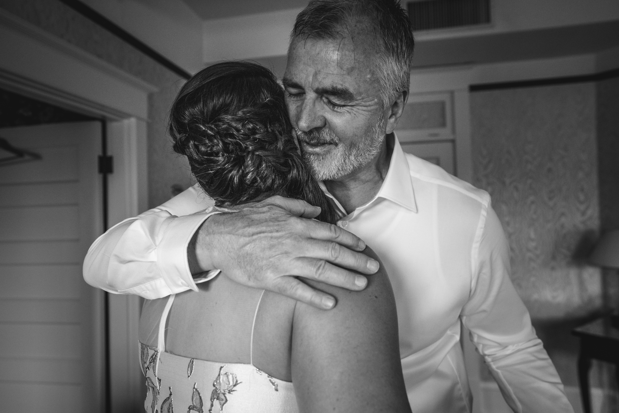 Black and white photo of the father-of-the-bride hugging his daughter after seeing her for the first time in her wedding dress. Taken in her hotel suite at the Hotel Boulderado in Boulder, CO.