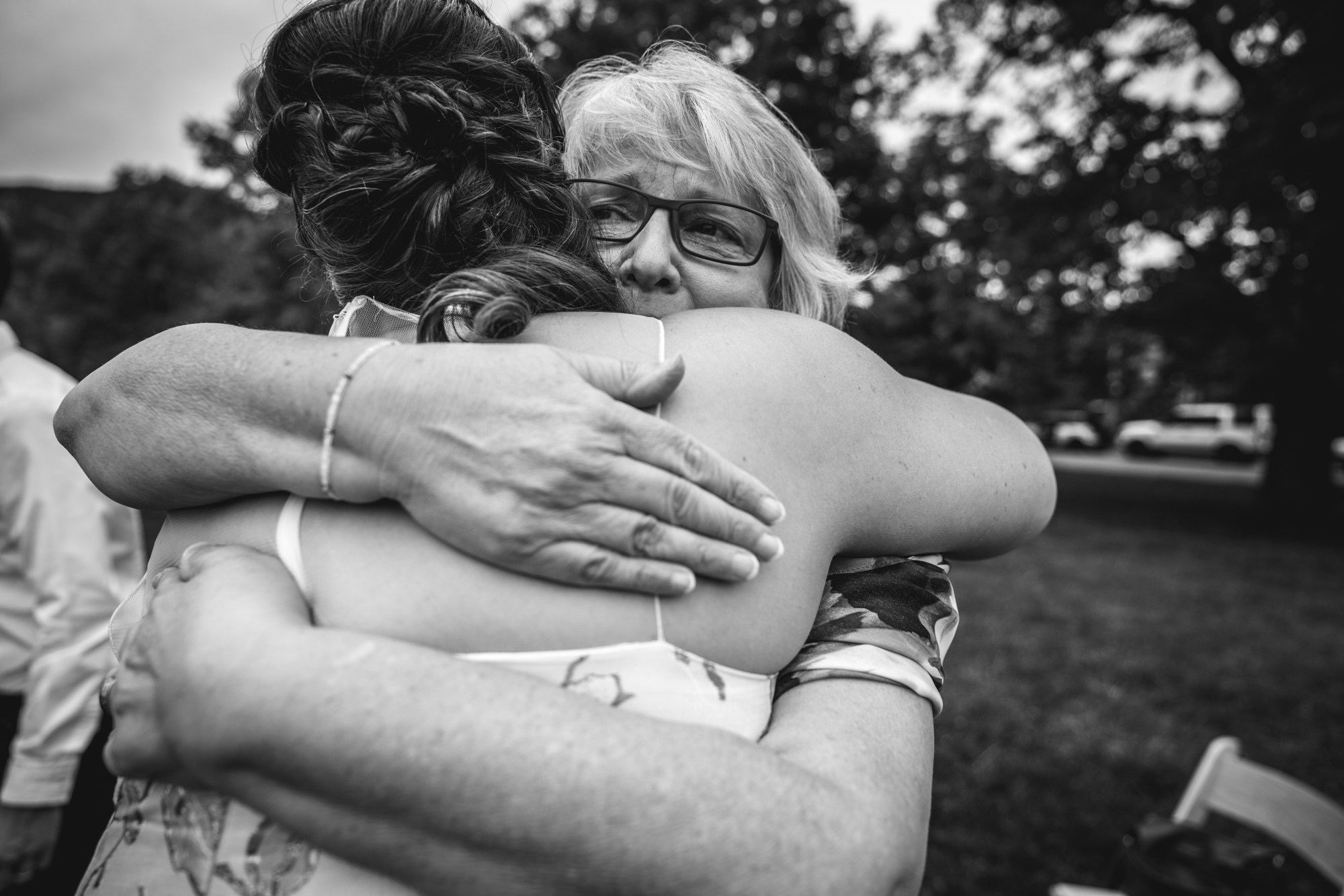Black and white photograph of a bride's new mother-in-law hugging her lovingly after the ceremony in Chautauqua Park in Boulder, Colorado.