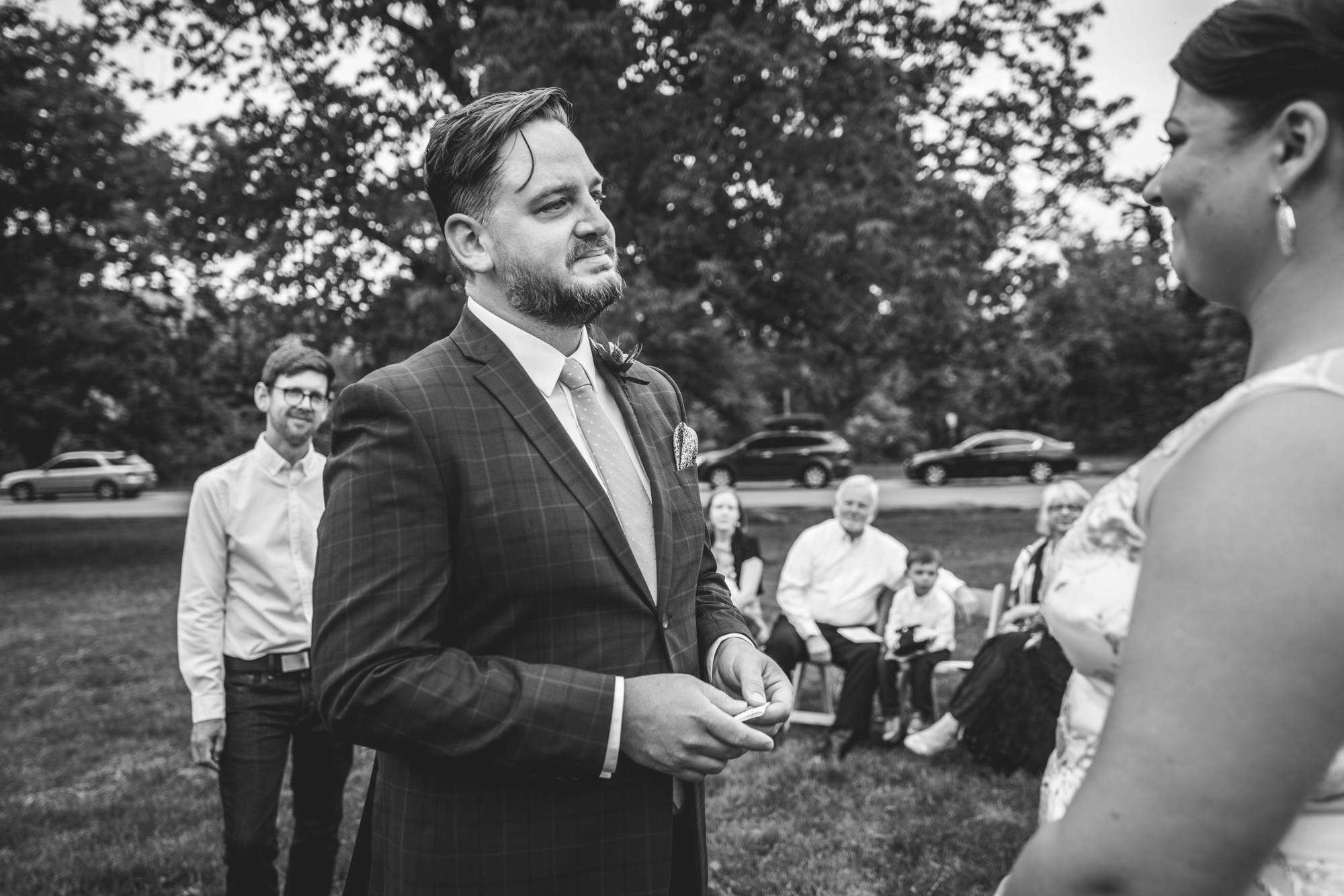 Black and white photo of a groom looking at his bride and crying during their wedding ceremony in Chautauqua Park in Boulder, Colorado.