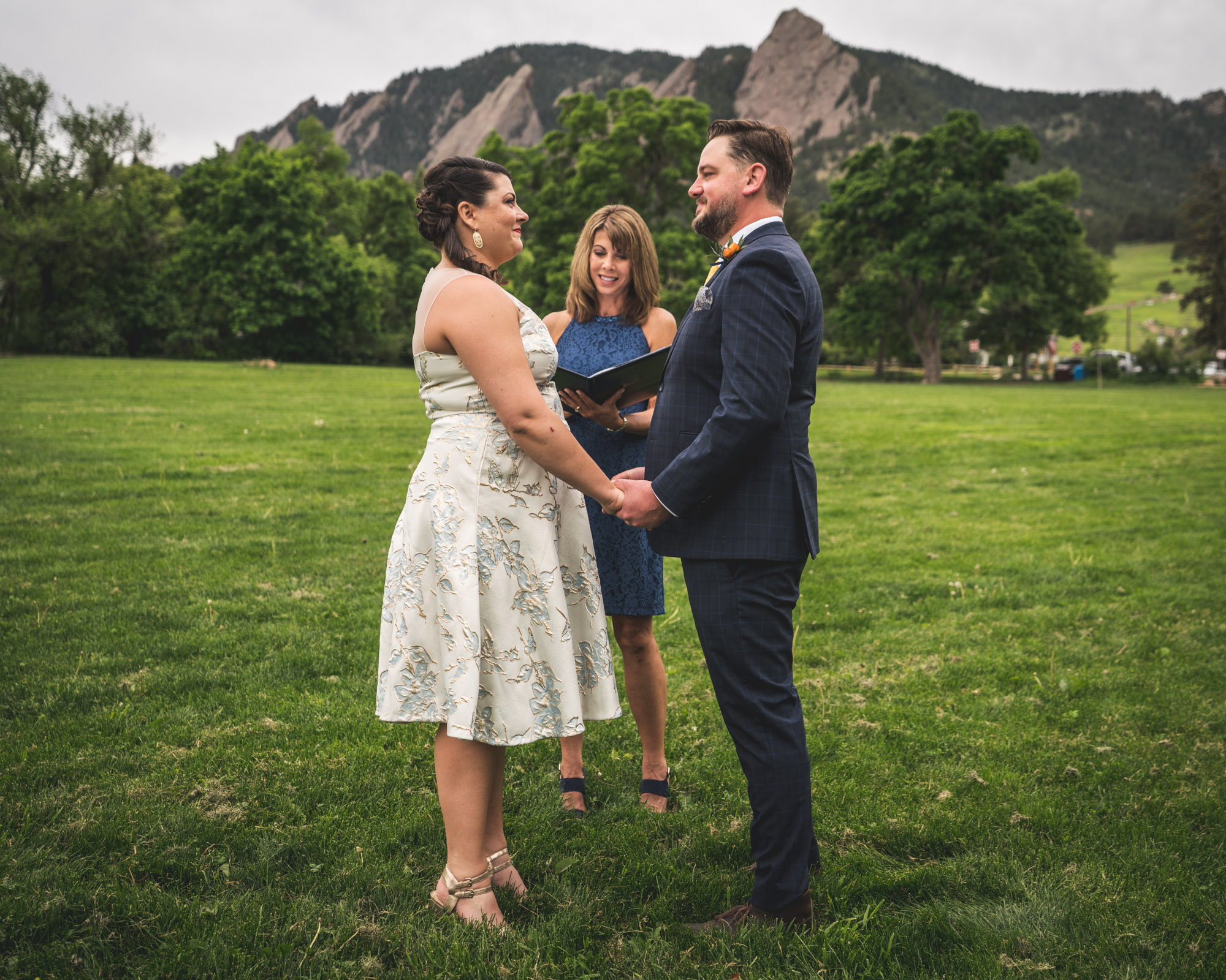 Color photo of a bride and groom getting married in deep green grass with the Flatirons looming in the background in Chautauqua Park in Boulder, Colorado.