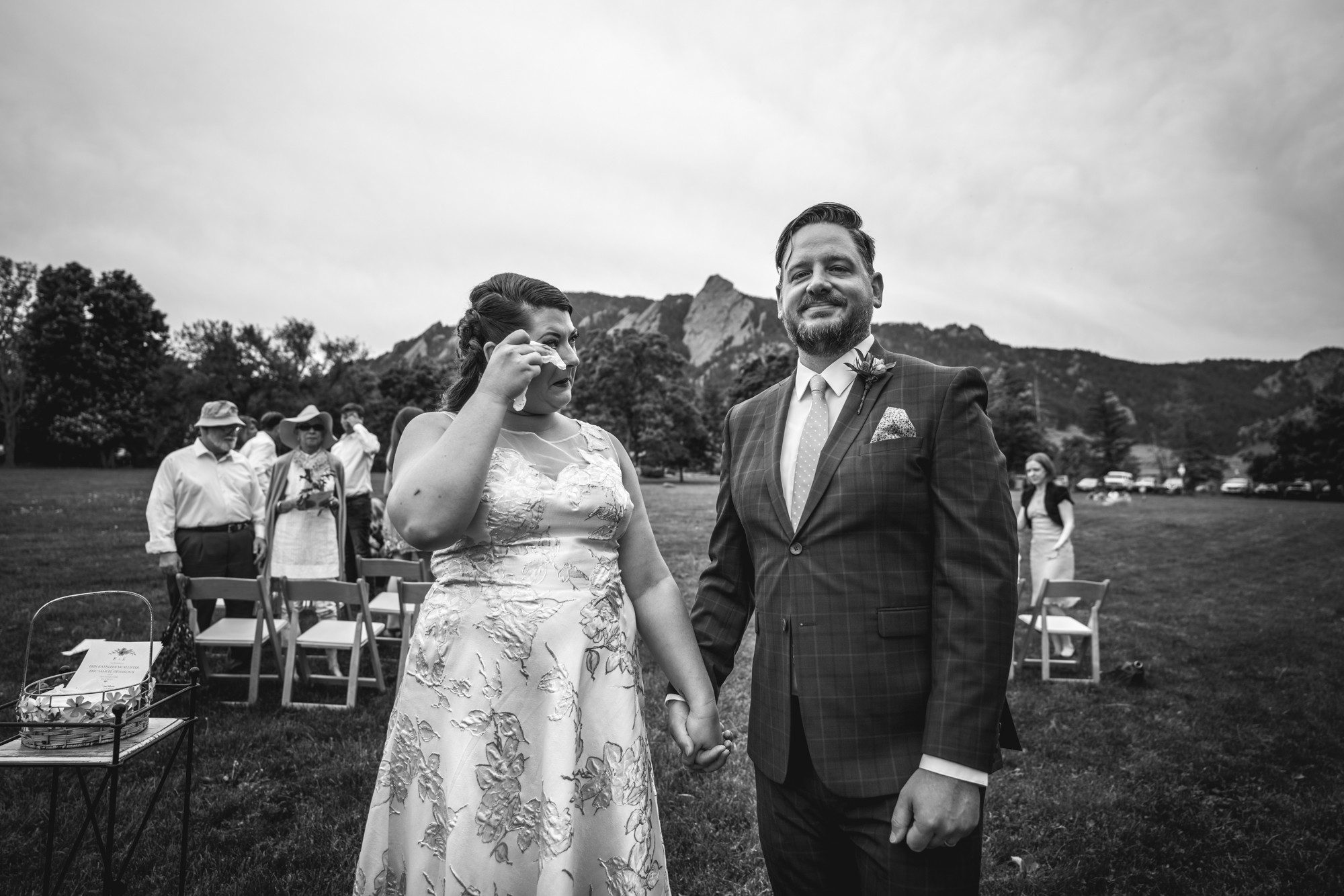 Black and white photo of a couple holding hands and crying happy tears immediately following their wedding ceremony in Chautauqua Park in Boulder, Colorado.