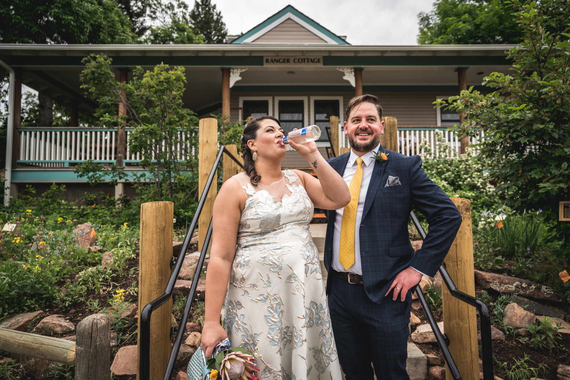 Color image of a bride tilting up her Zima and drinking it while holding her bouquet as her husband smiles and waits for her to finish it. Taken at the visitor's center in Chautauqua Park.