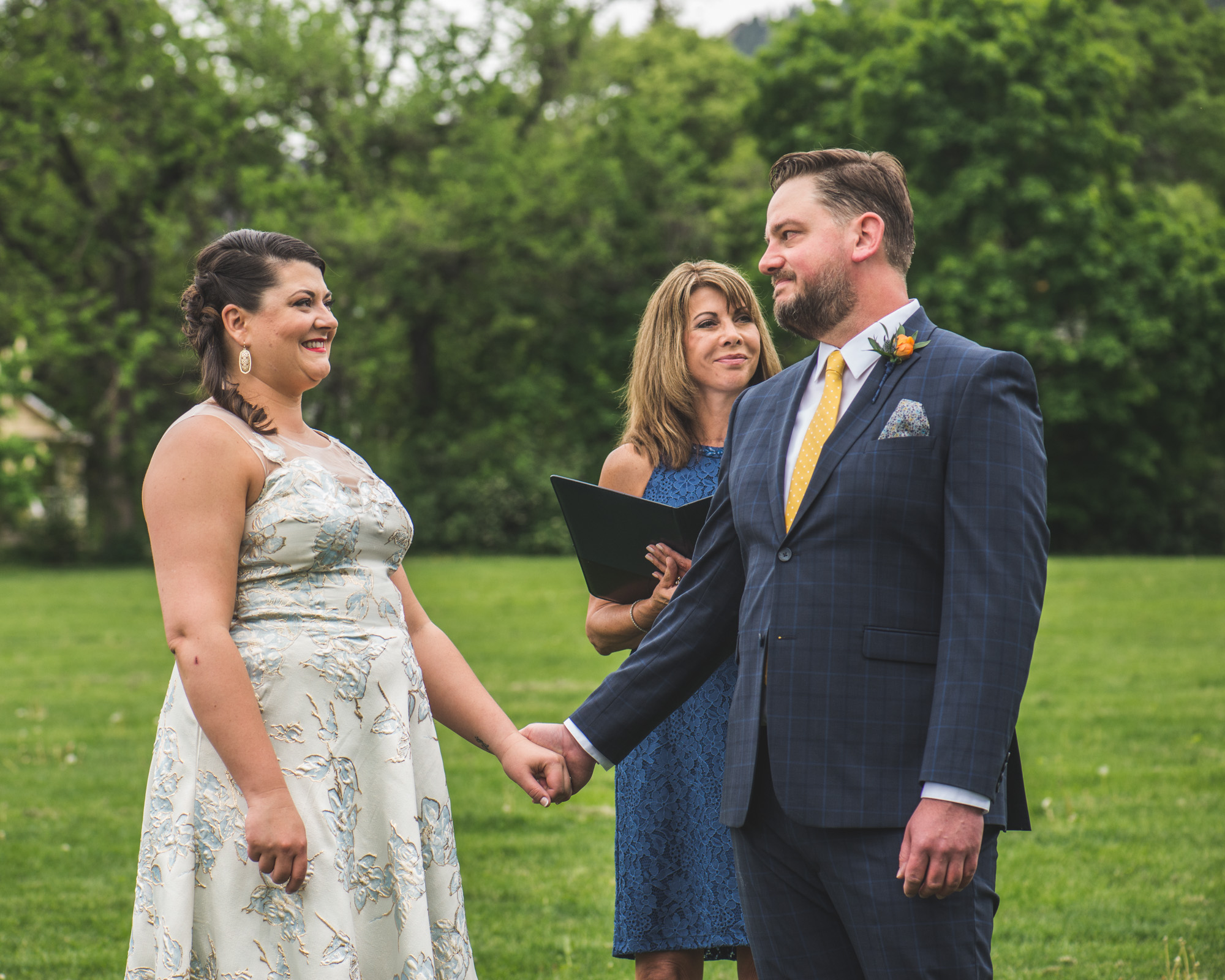 Color photograph of a groom looking lovingly at his bride during their wedding ceremony in Chautauqua Park in Boulder, CO.