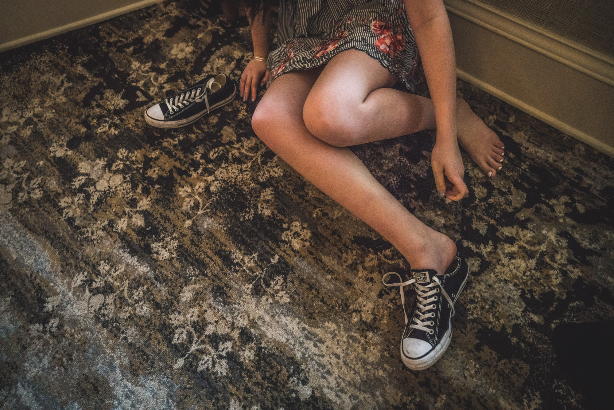 Color photo of a girl sitting on the ground in a dress and putting on black and white sneakers.