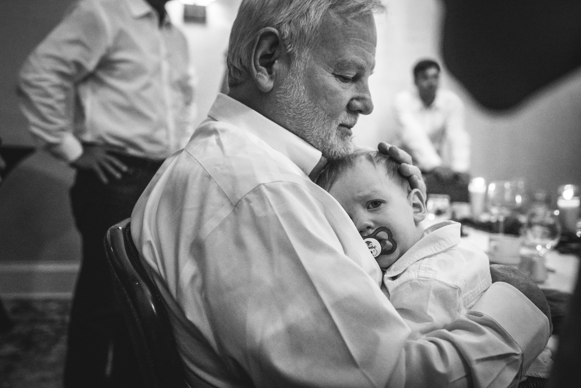 Black and white image of a grandpa and grandson at a wedding table, the little grandson lying his sweet head on his grandpa's chest as he pouts.