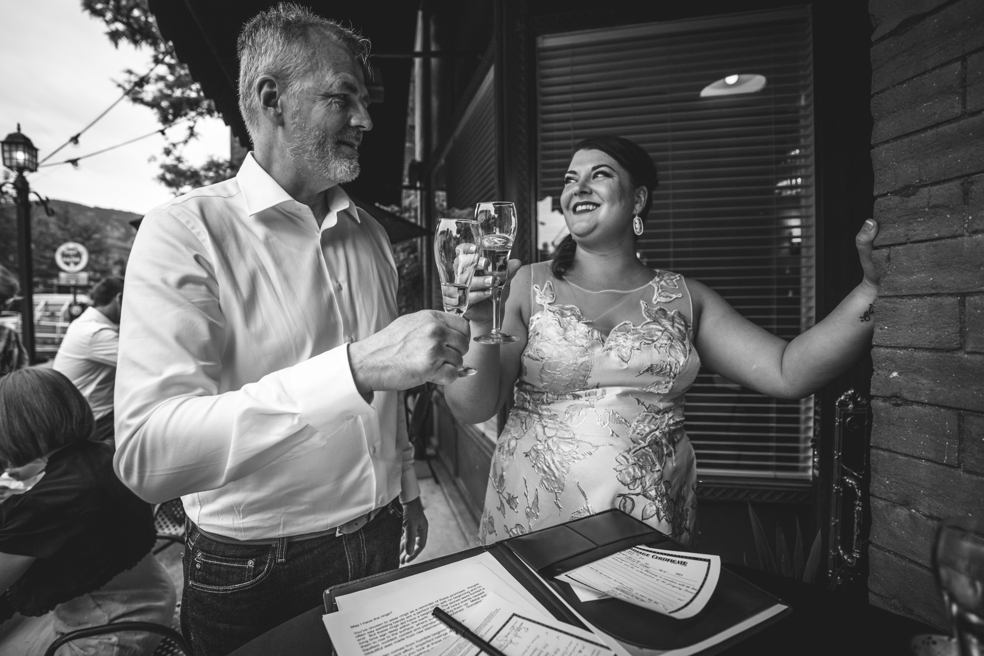 Black and white photograph of a bride and the father of the bride toasting with a glass of champagne at her wedding reception at the Hotel Boulderado.