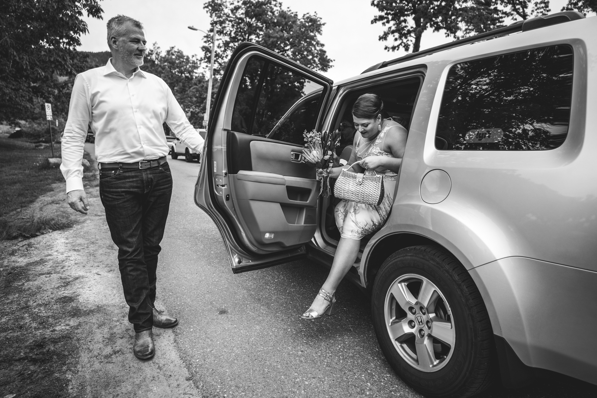 Black and white photo of a father opening the car door for his daughter, the bride, as she gets out in preparation to walk down the aisle.