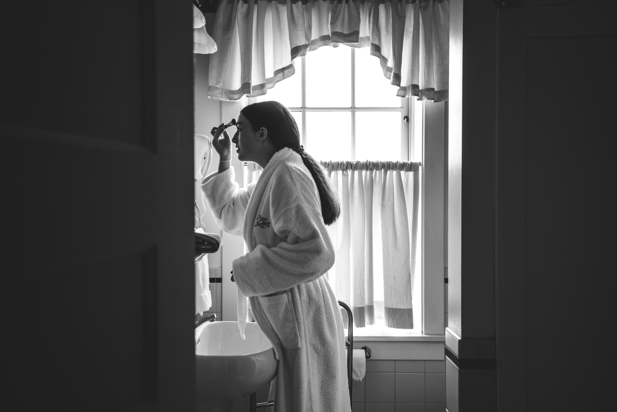Black and white photo of a young woman wearing a robe in a beautifully lite bathroom putting makeup on in the mirror. Taken in the Hotel Boulderado in Boulder, Colorado.
