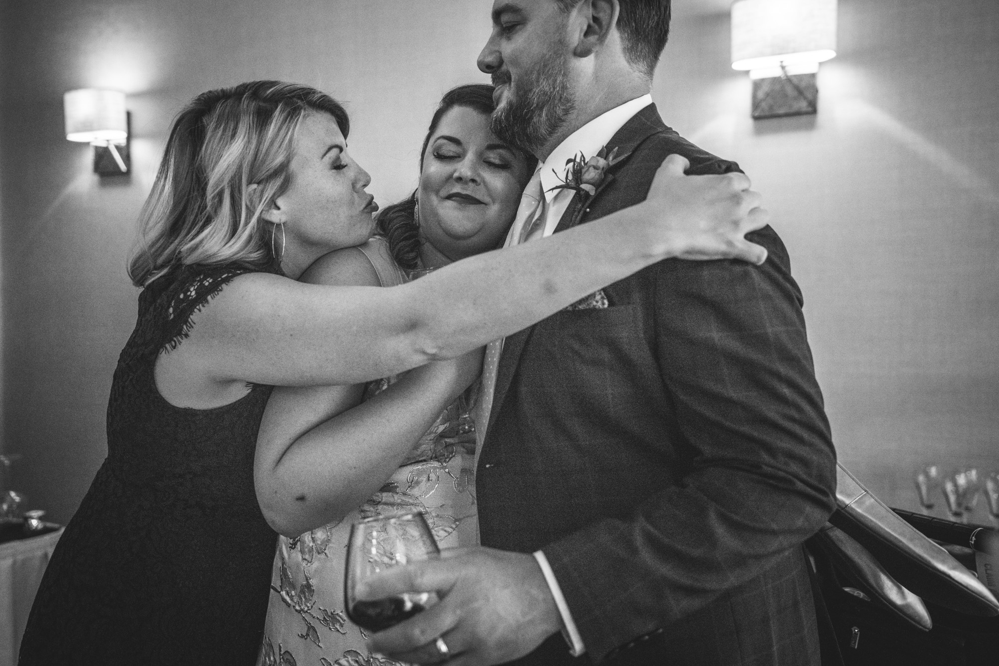 Black and white photograph of the maid of honor at a wedding reception hugging both the bride and groom while making a funny kissy face