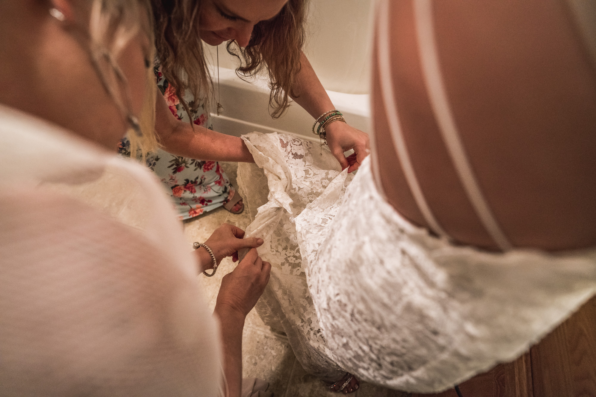 Overhead color photograph of two women attempting to bustle a bride's dress