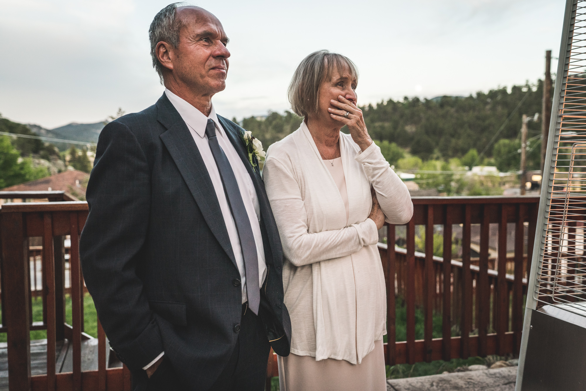 Color photo of a mother and father standing on a deck with rolling green mountains in the background, crying as they watch their daughter have her first dance with her husband on their wedding day.
