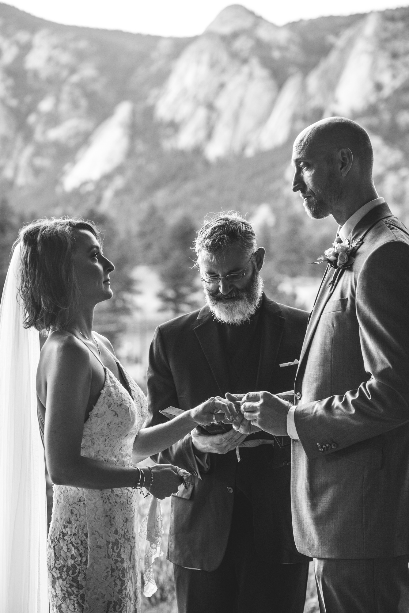 Close up black and white photo of a wedding ceremony in which the bride and groom look lovingly at one another while the groom puts the ring on the bride's finger.