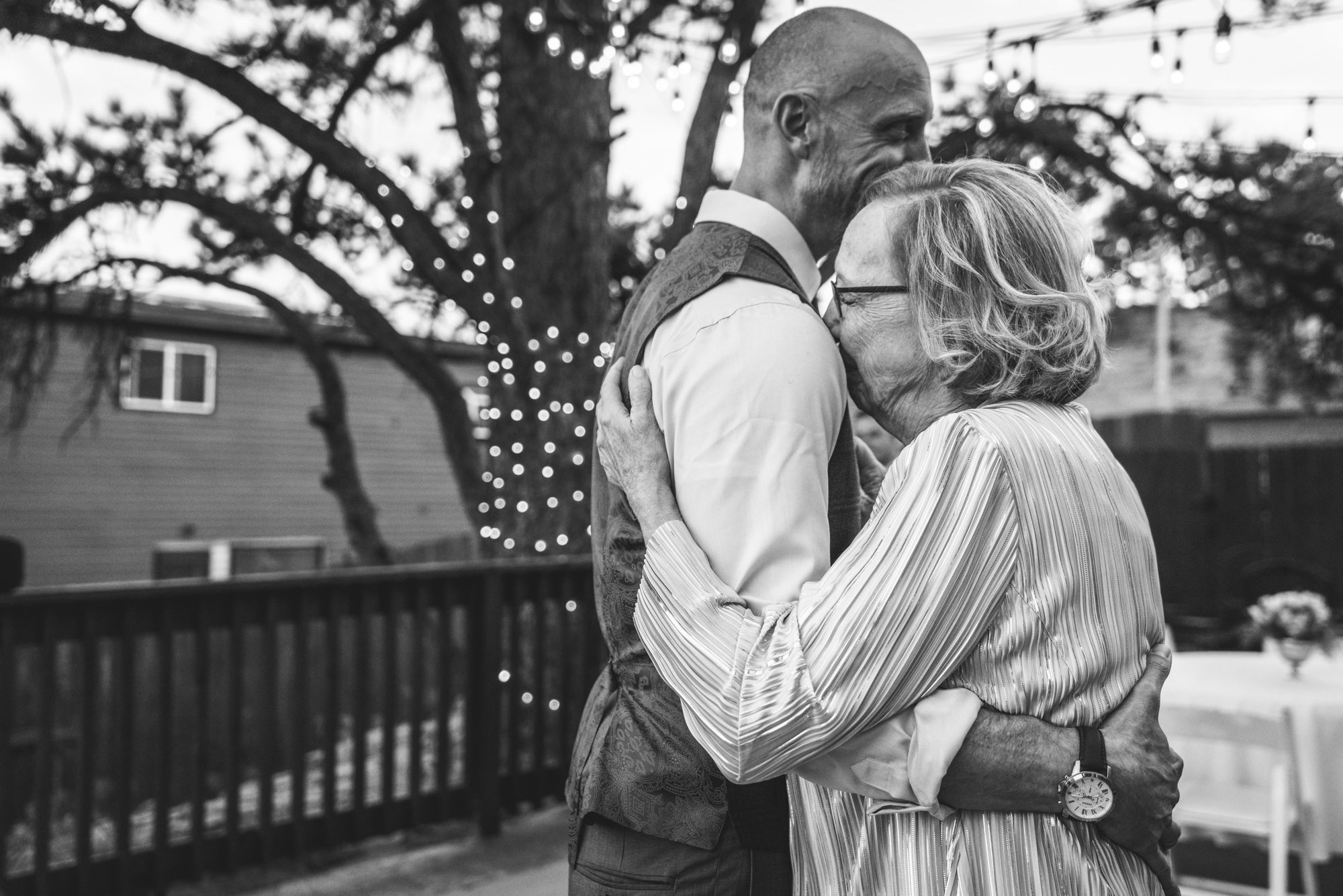 Black and white photo of an outside wedding reception with Christmas lights on a tree in the background as a mother lays her head on her son's shoulder and cries as they dance. Taken in Estes Park, Colorado.