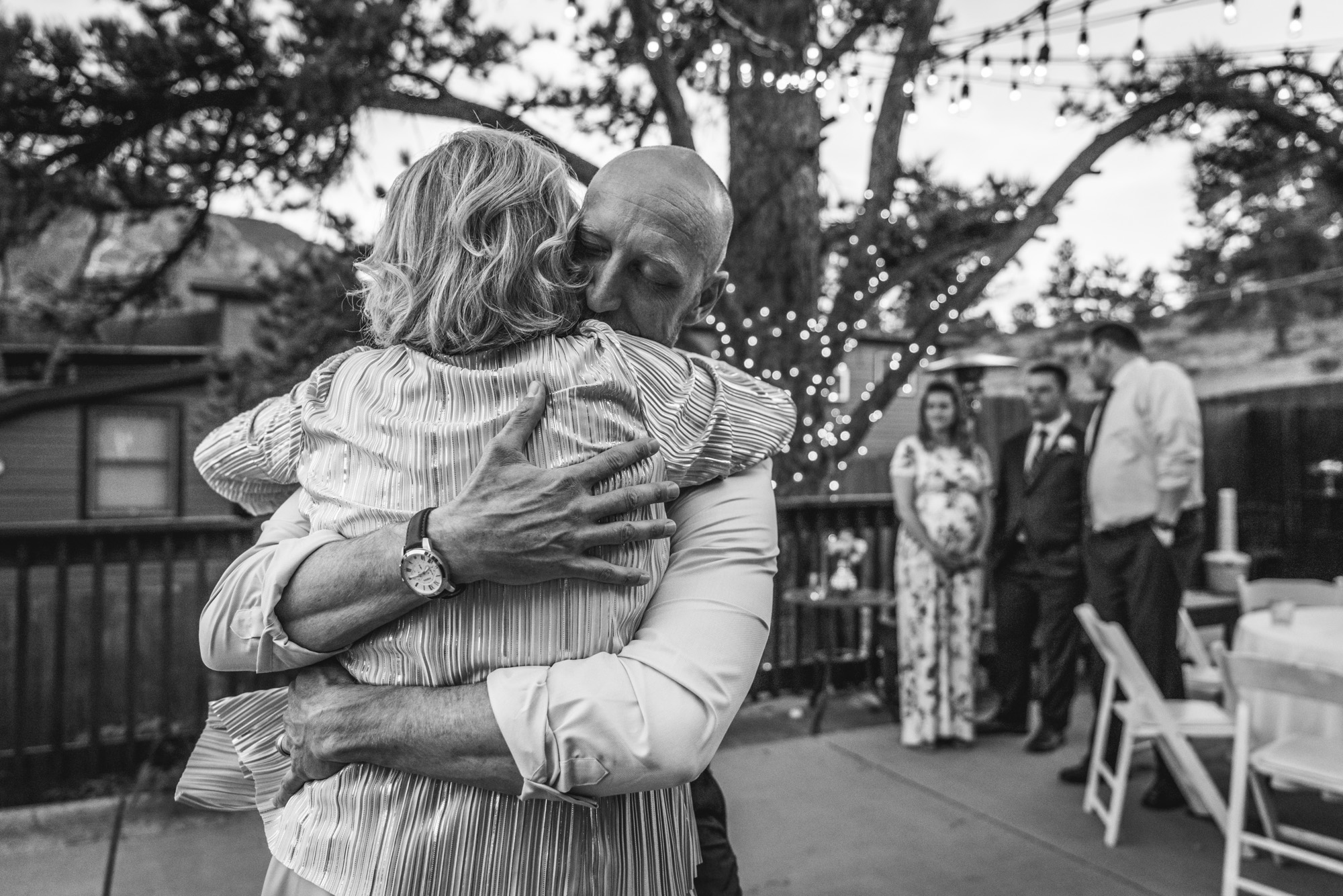 Black and white photograph taken at a wedding reception in which the son hugs his mother during their first dance.