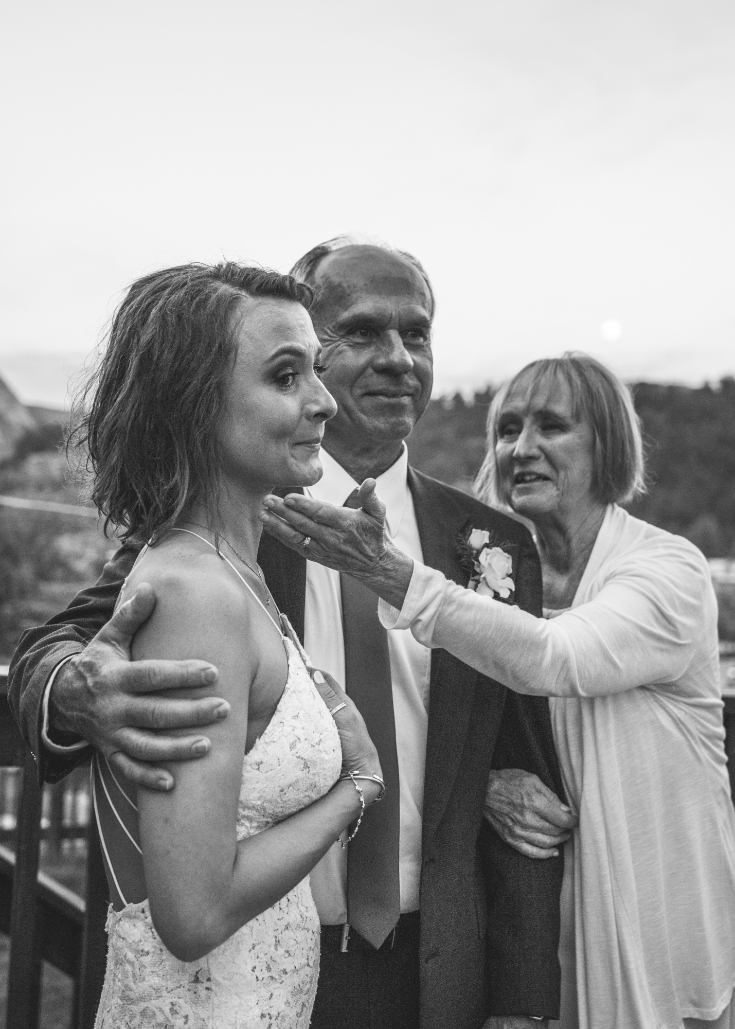 Black and white vertical image of a bride huddled together with her parents on the day of her wedding. The bride cries as she watches something off scene as her mother moves to place her hand on the bride's cheek. Taken during a wedding reception at the Bristlecone Inn in Estes Park, CO.